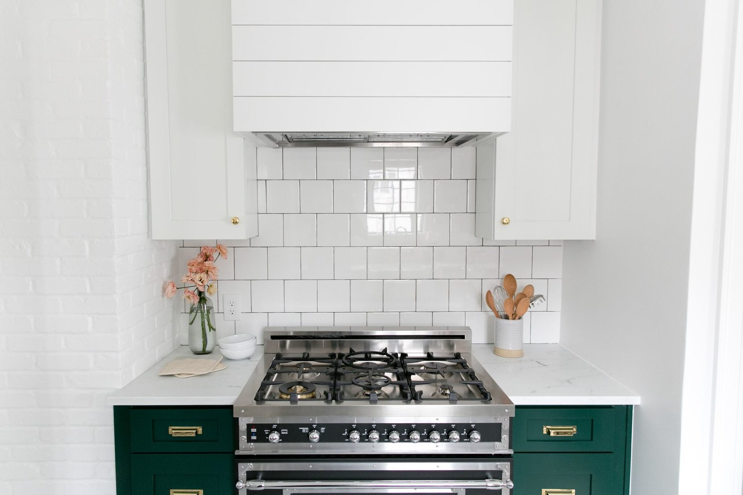 Open range oven against green cabinets in kitchen