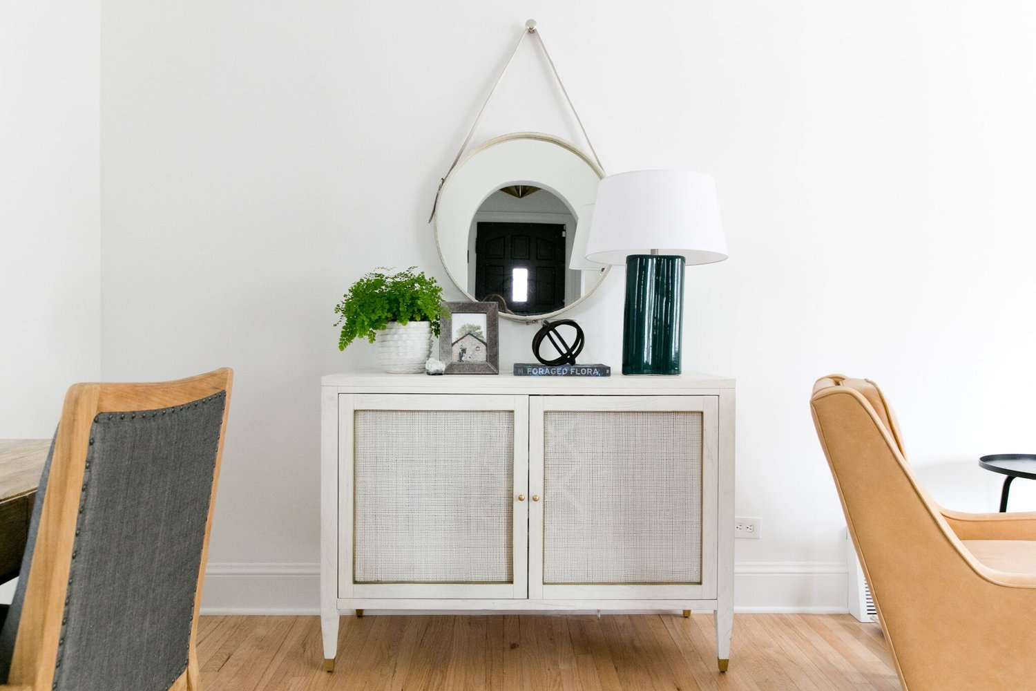 white hutch with round mirror in hall