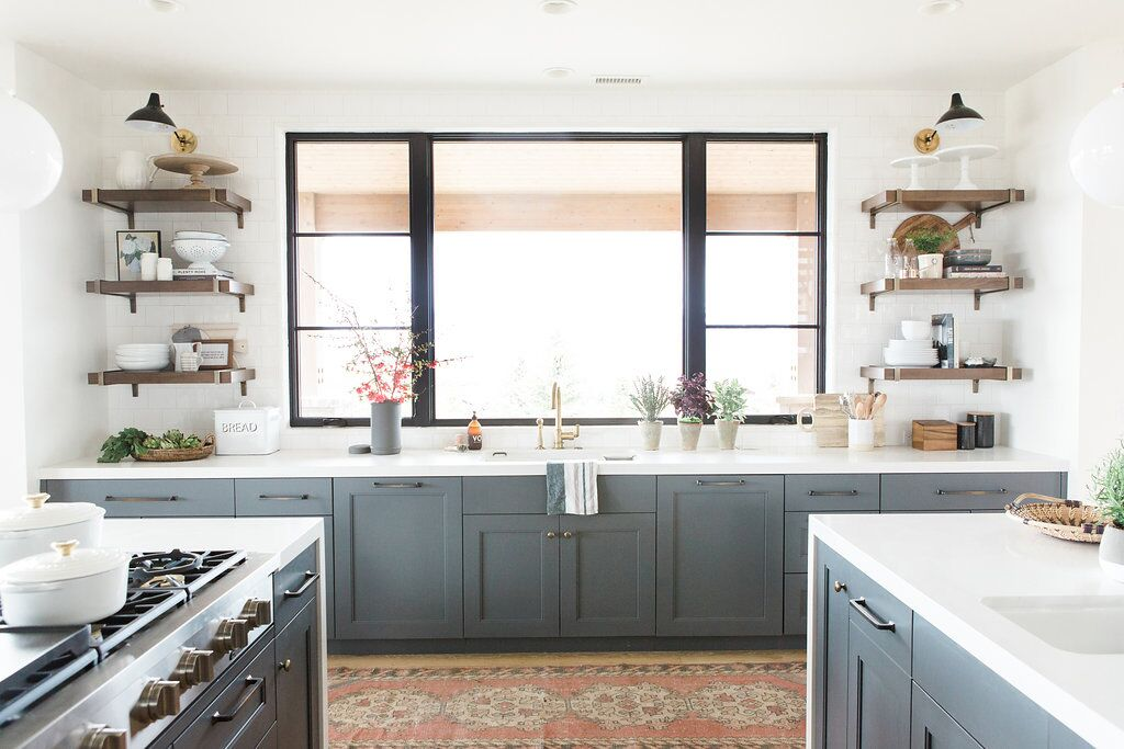 Modern kitchen with open shelves, vintage rug, and blue cabinets with white countertops