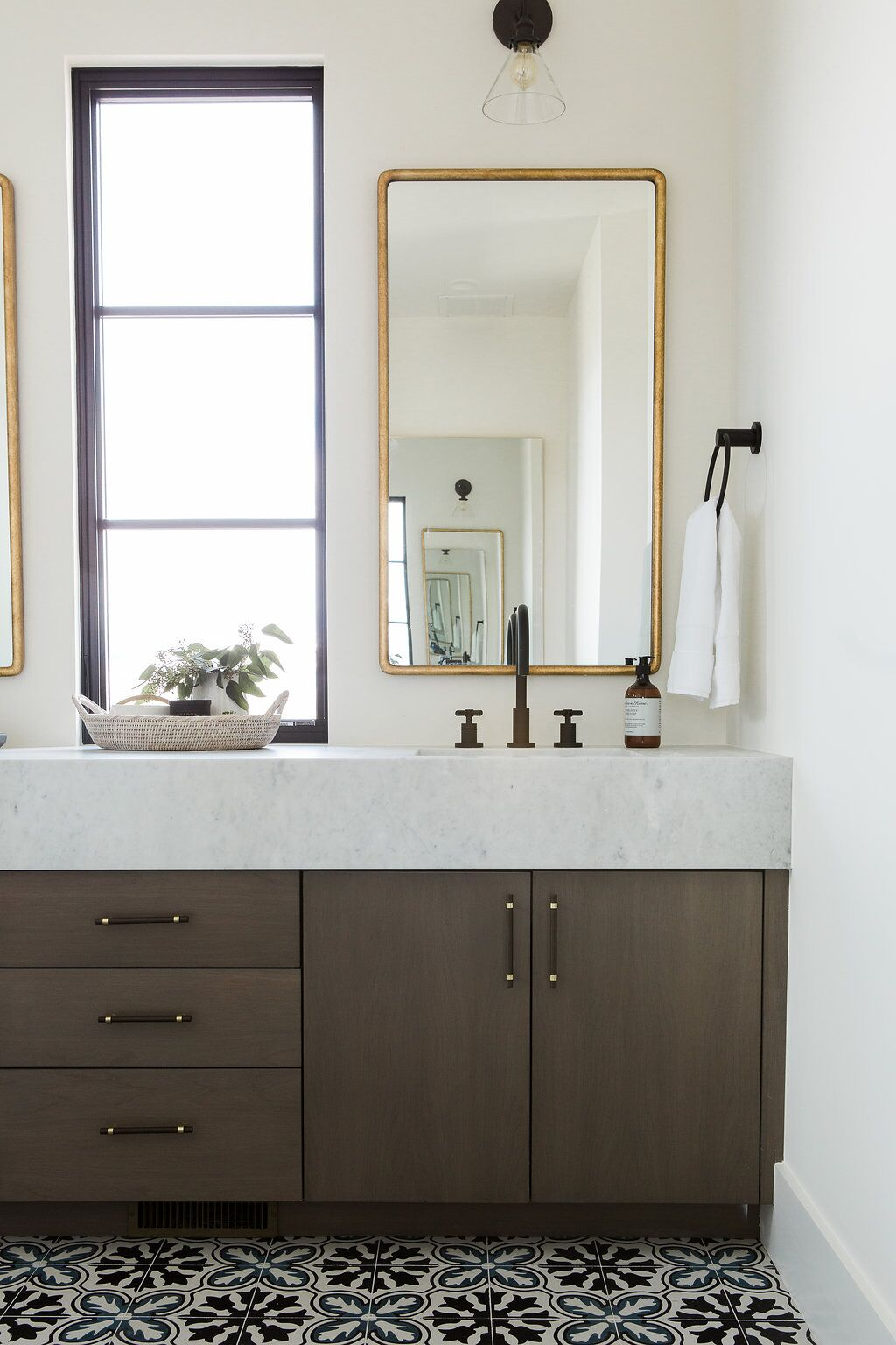 Guest bathroom with double vanity, gold mirrors, and patterned tile