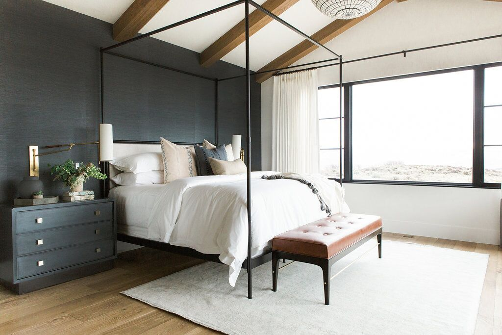 Master bedroom in blue grasscloth wallpaper, statement chandelier, and leather bench