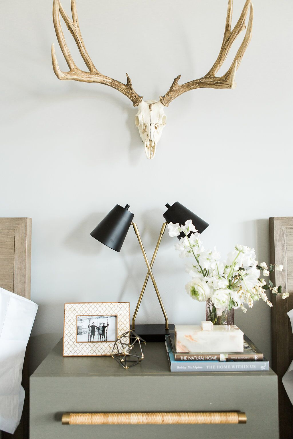 Neutral guest bedroom with matching beds and hanging antlers