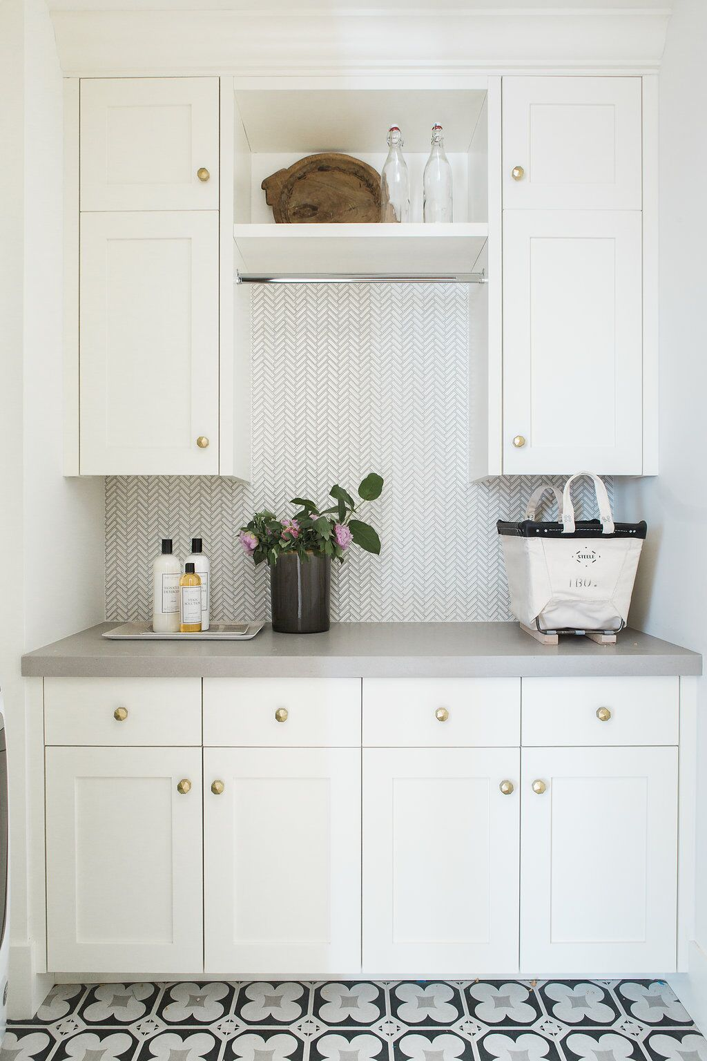 Laundry room with patterned wallpaper and concrete tile
