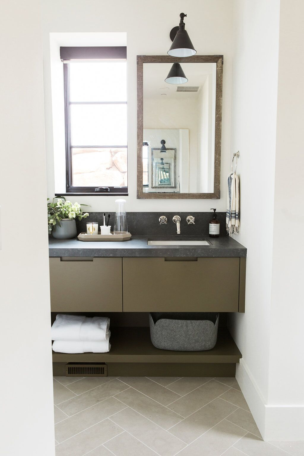 Guest bathroom with olive green cabinets and dark countertops and limestone herringbone floors