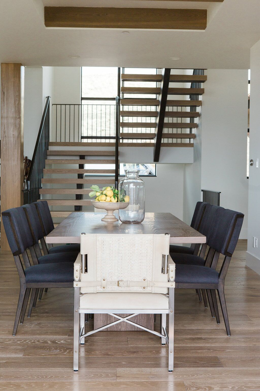 Long table with grey chairs and staircase in background