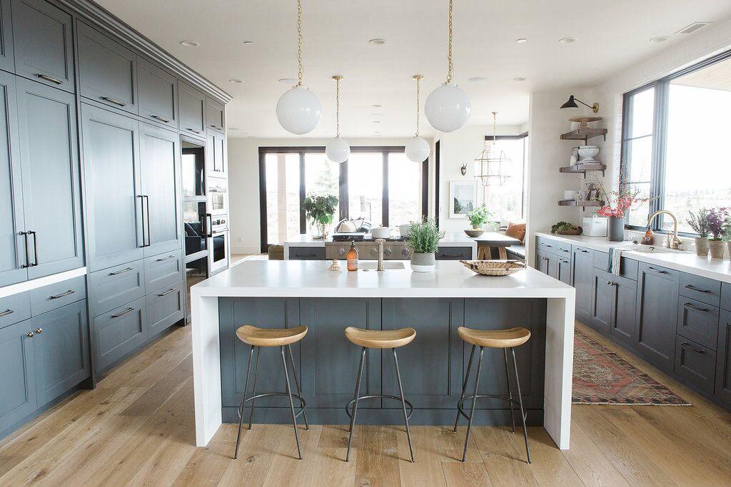 Three wooden stools underneath modern kitchen island