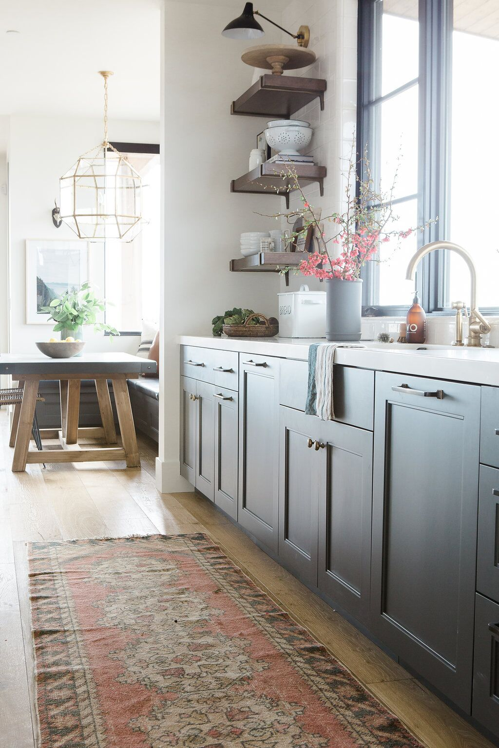 Grey cabinets with white counter top and faucet