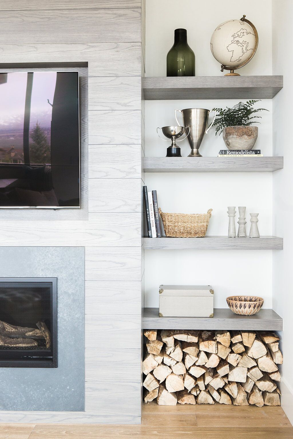 built in grey shelves and stacked logs beside fireplace
