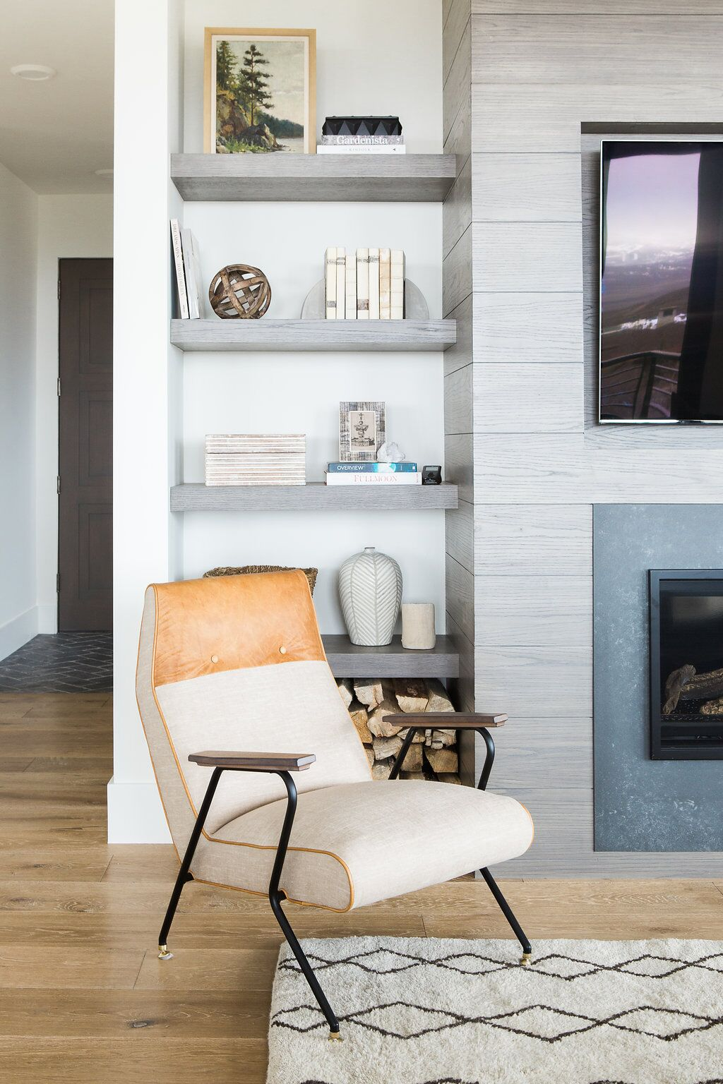 Modern white chair with bronze top in front of shelves