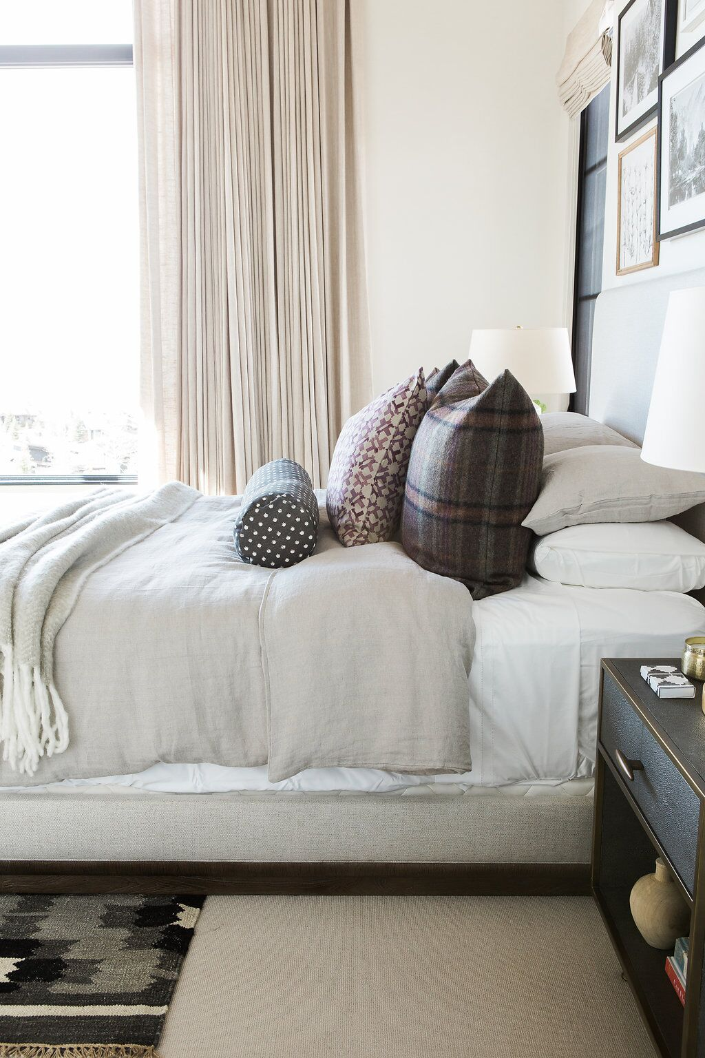 Side of bed with pile of formal pillows