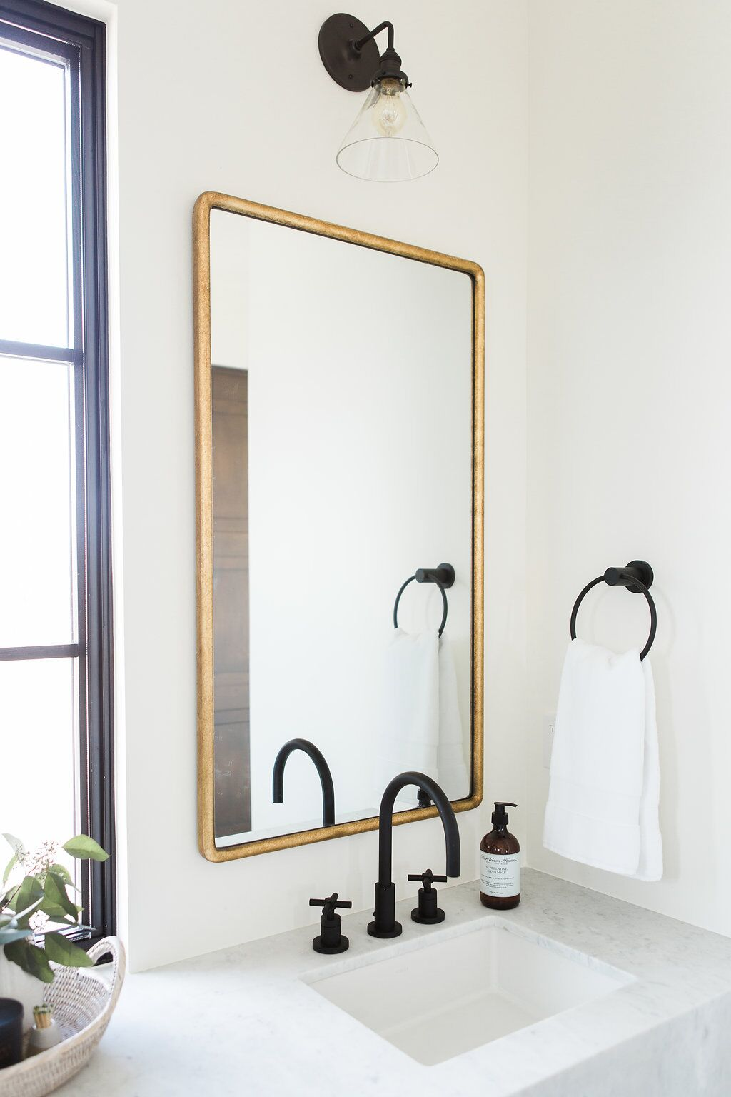 Gold mirror behind faucet in master bathroom