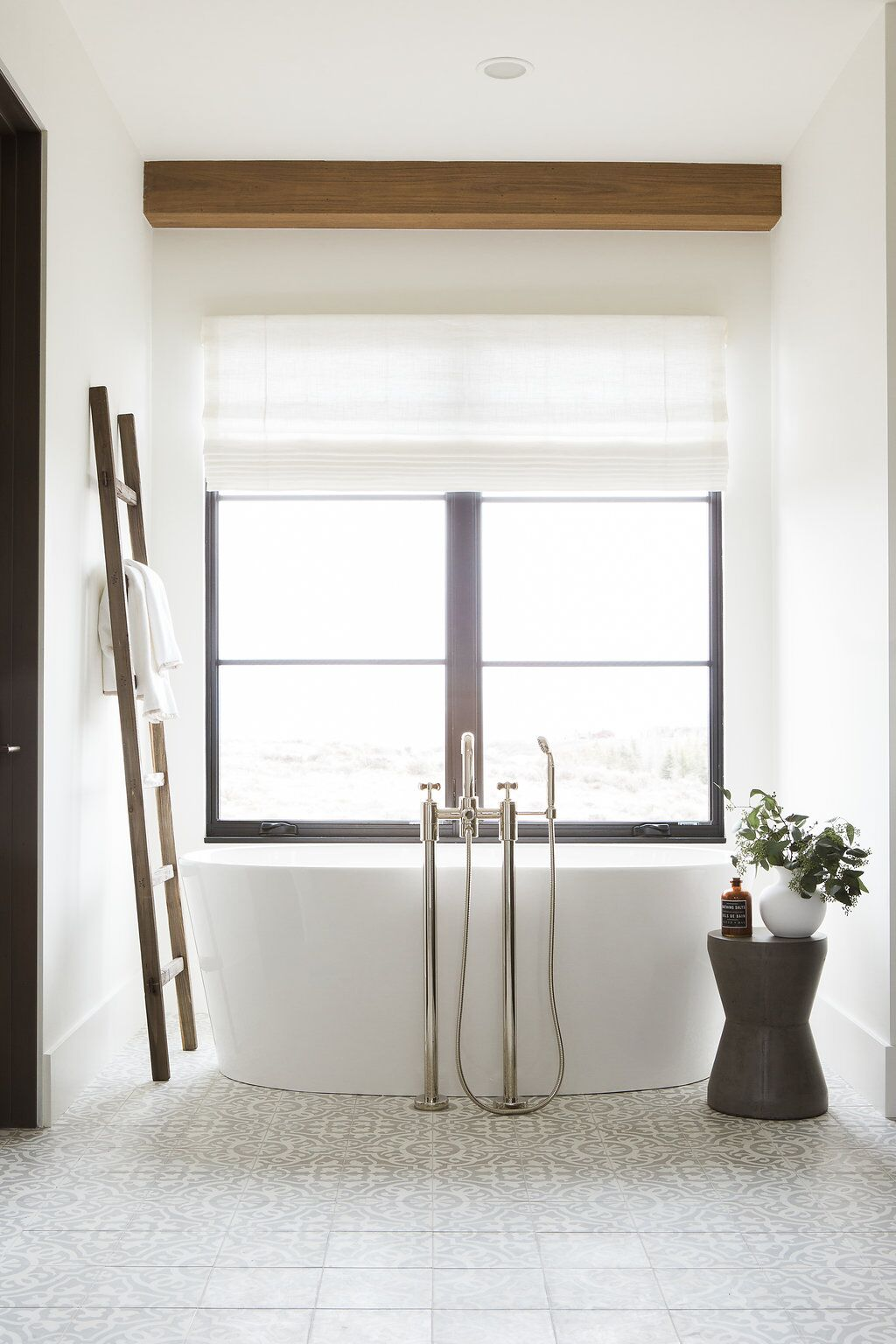 Large white, stand alone tub in front of window