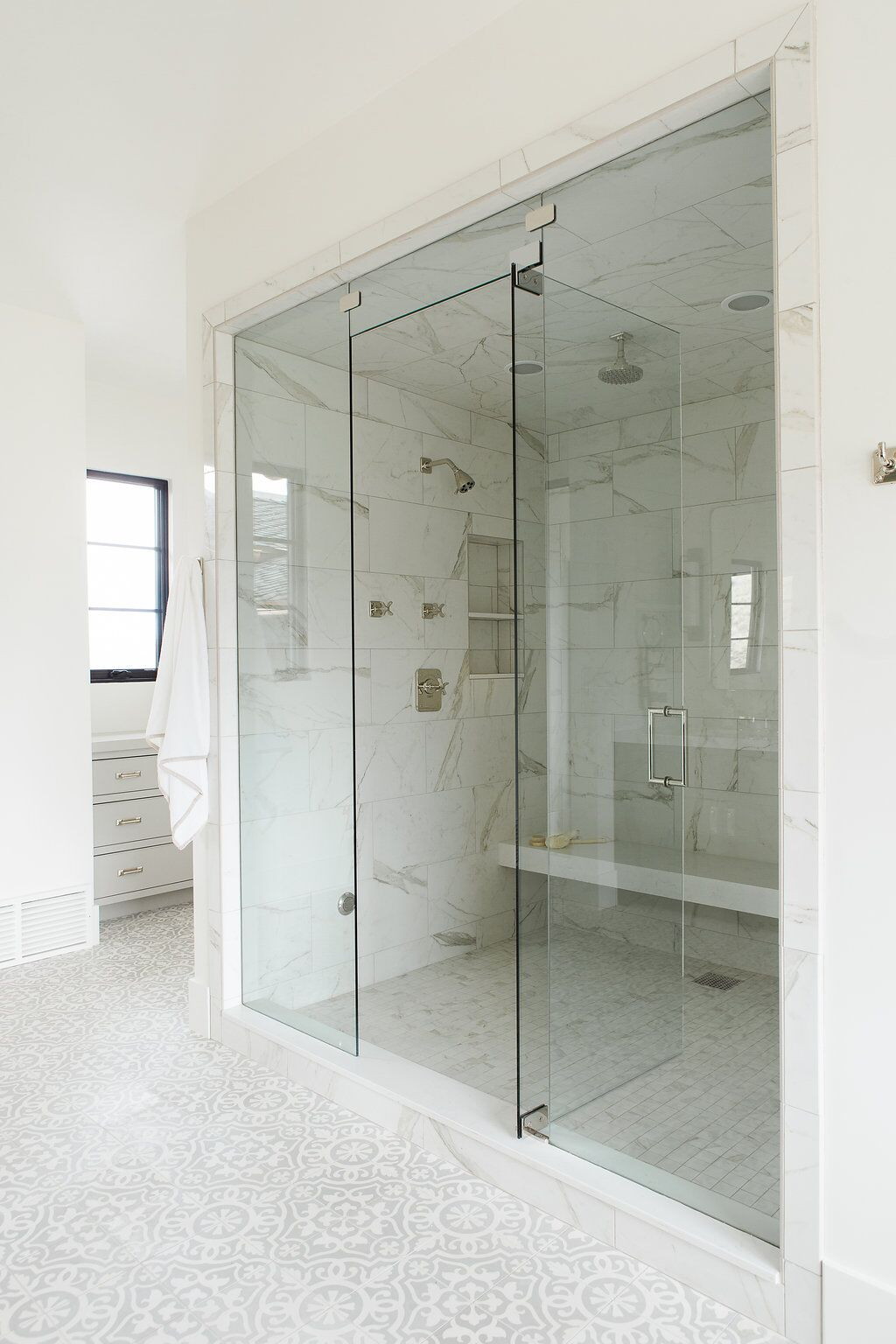 Stone bench in large shower in bathroom
