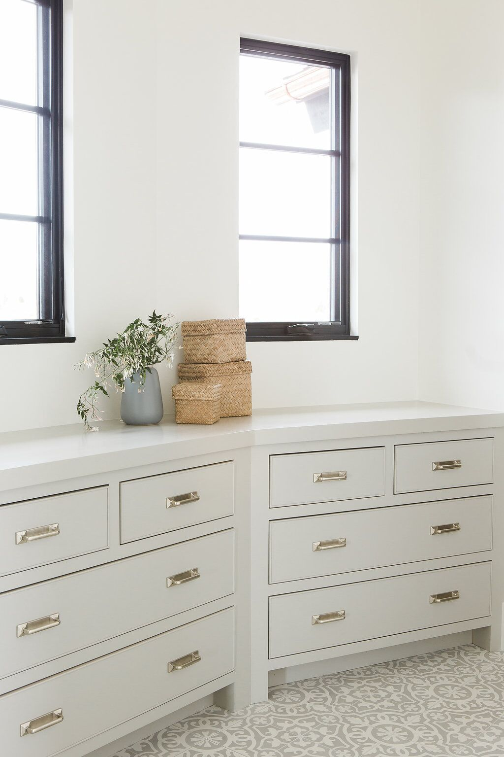 White cabinets in front of two small windows