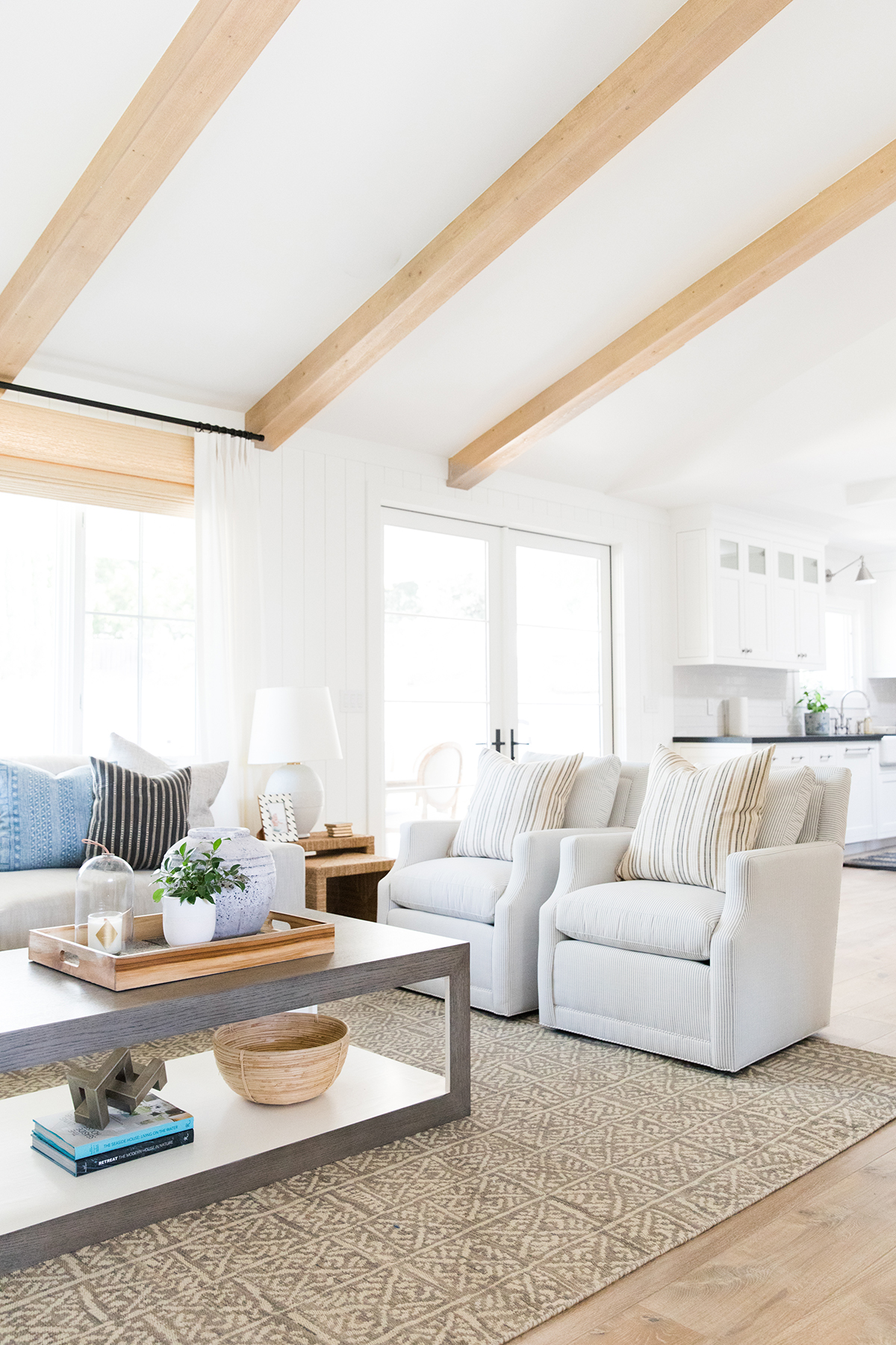Moody coastal living room with roman shades and exposed beams.jpg