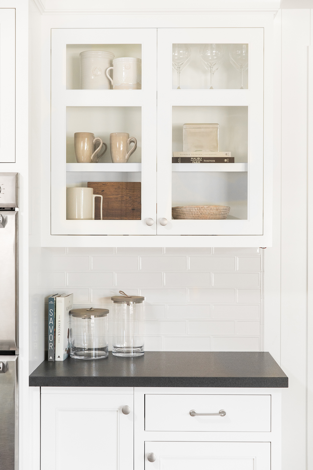 Kitchen cabinetry with clear glass, dark countertops-Studio McGee.jpg