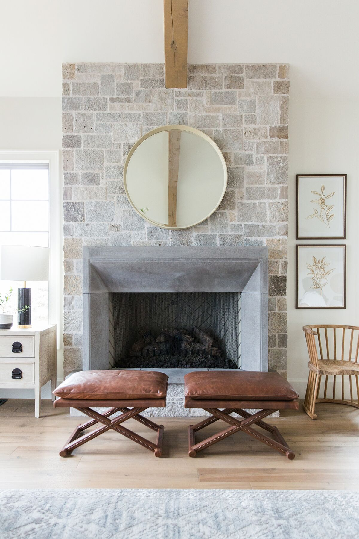 Stone fireplace with molded brick, leather x-stools, seating area by fireplace in mountain home - Studio McGee Design