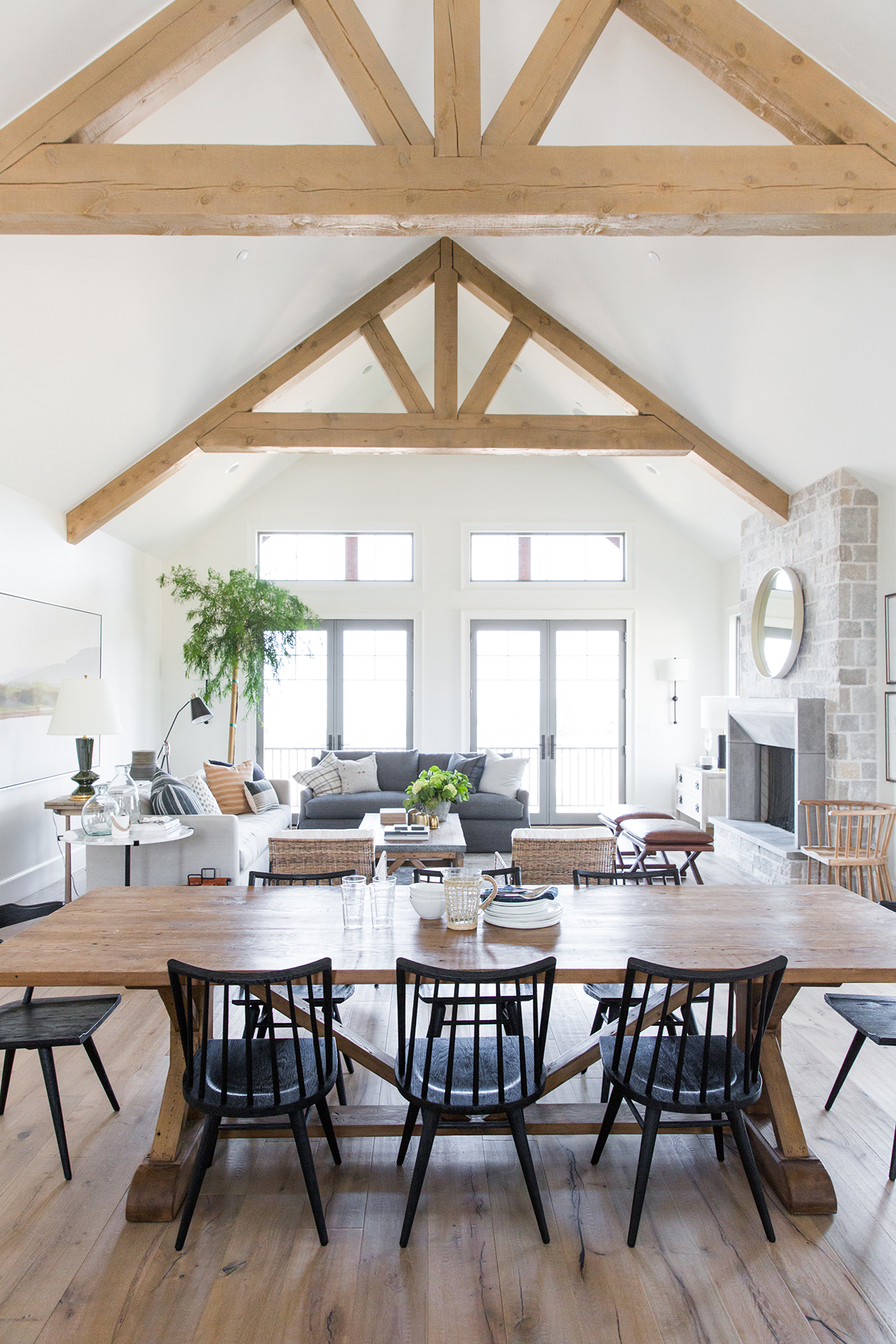 Dining room with exposed beams, mismatched chairs, black chairs in mountain home - Studio McGee Design