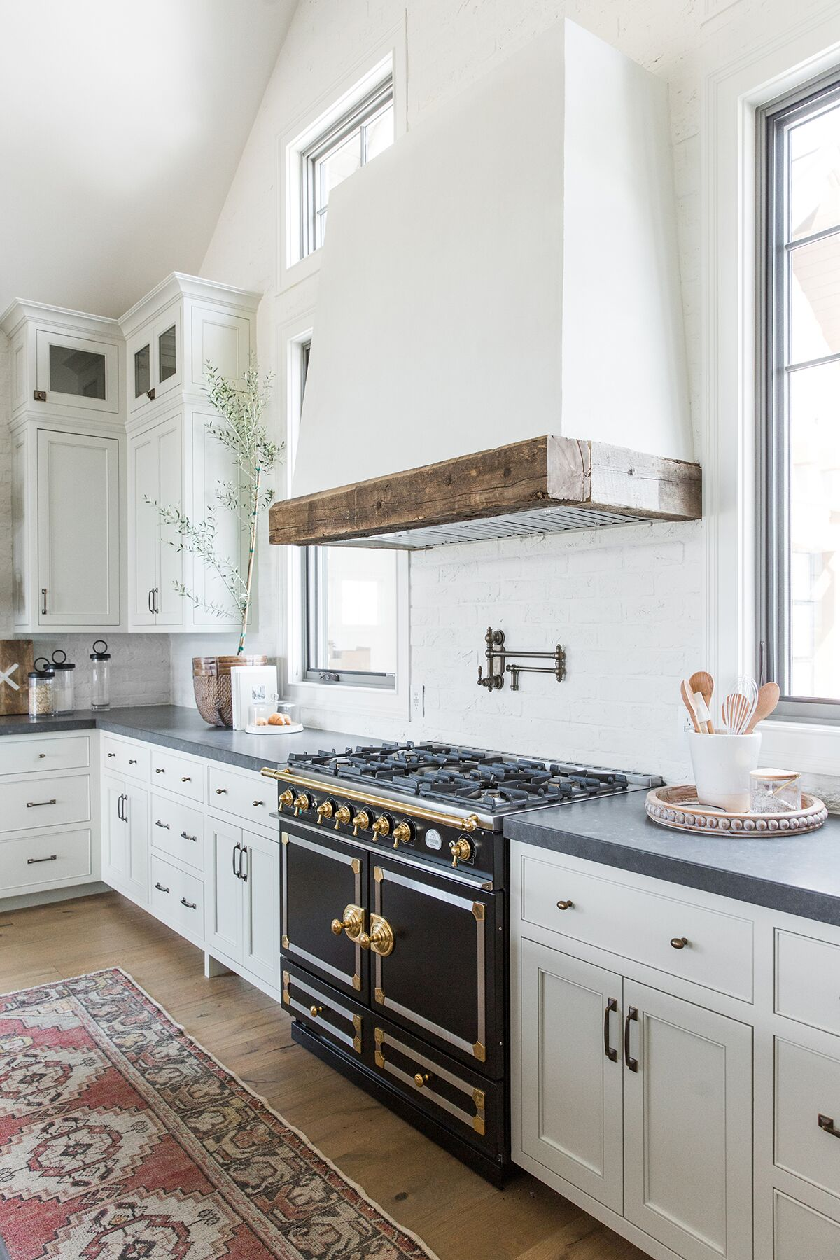 Refined,+rustic+kitchen+with+exposed+wooden+beams,+hanging+lanterns,+painted+white+brick,+oven+range+in+mountain+home+-+Studio+McGee+Design-2.jpg