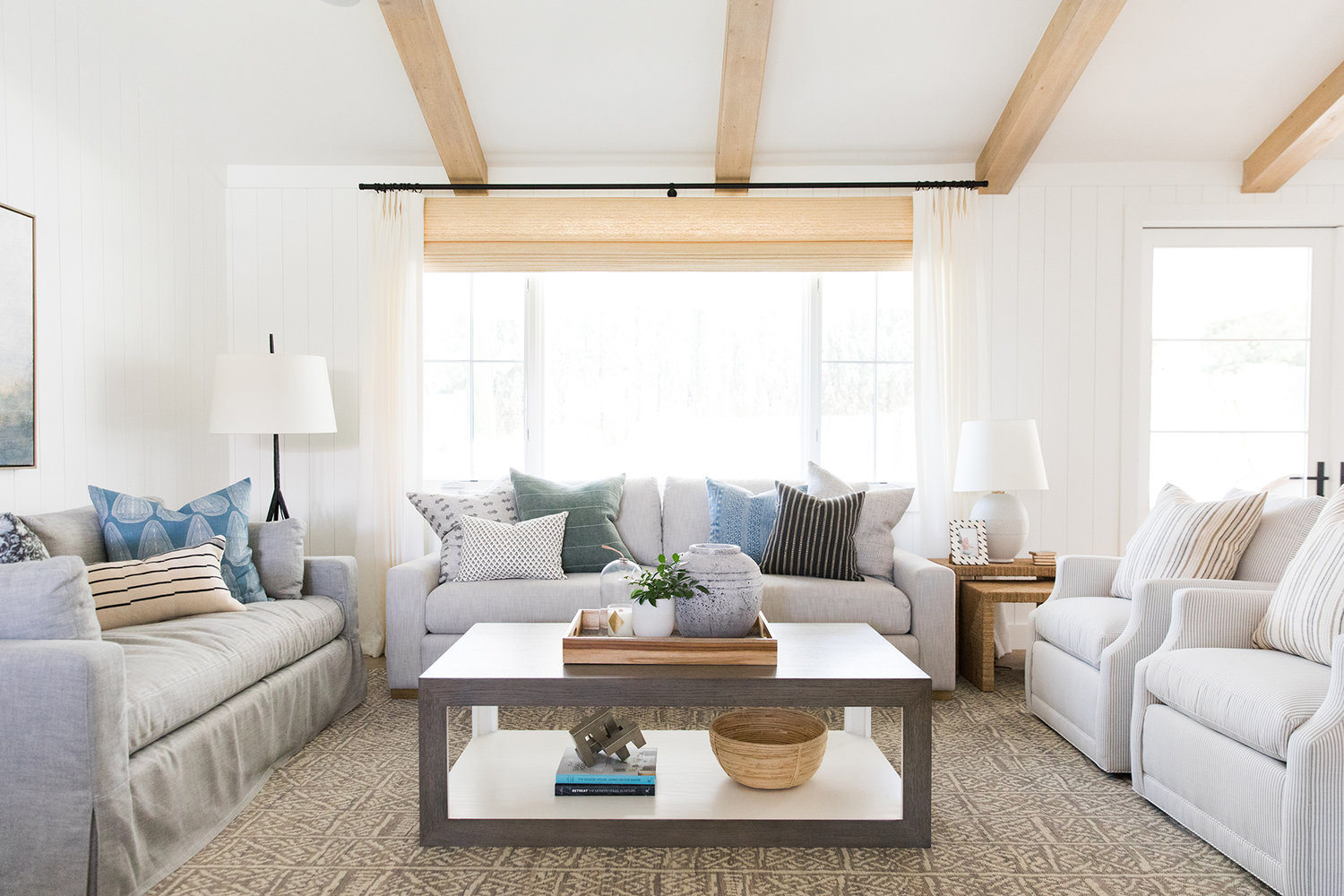 Moody+coastal+living+room+with+modern+art+and+exposed+beams.jpg