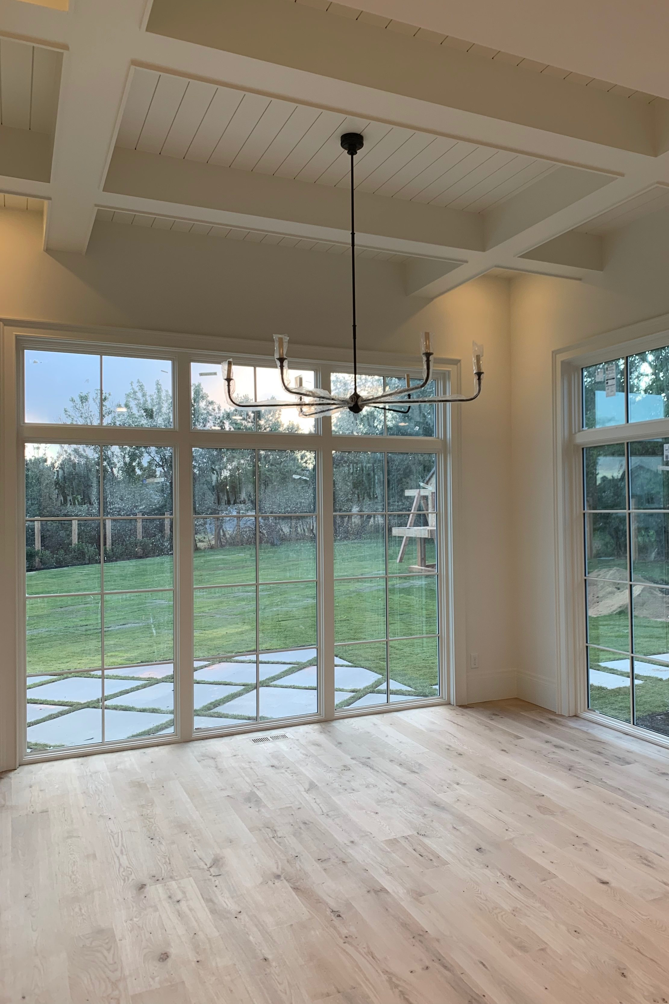 I love being able to look out the windows of our dining room and see where our trampoline and swing set are going to be! Beautiful ceiling treatments by  Metrie  make it even better.
