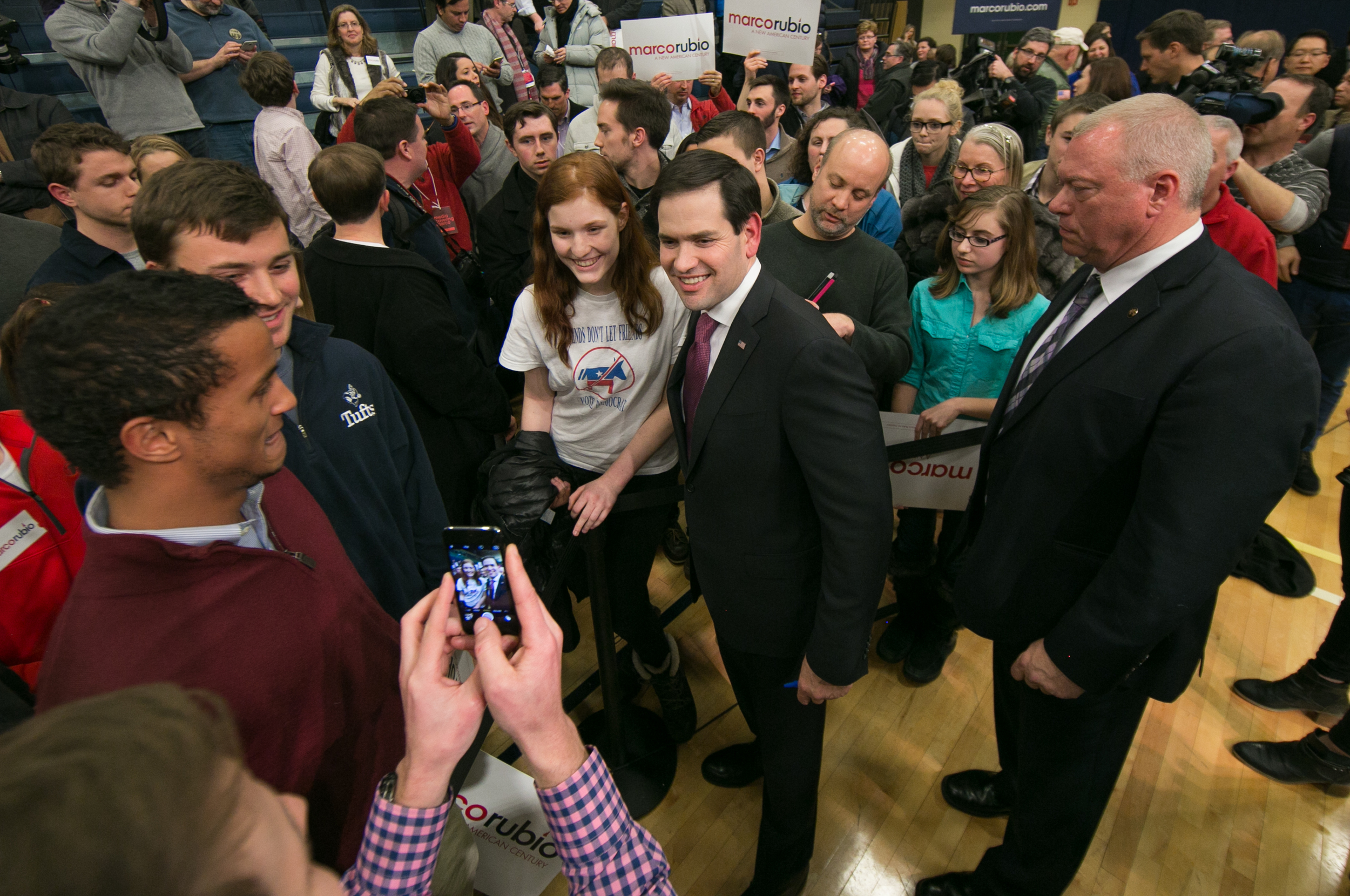 """February 8, 2016: Senator Marco Rubio, a republican candidate in the United States presidential primary, poses for a photo with Emily Carlson, 15, of Manchester NH, after giving a speech during a political rally at 505 Amherst St., in Nashua, New Hampshire. Carlson was also eager to have Rubio sign the back of her shirt, which plainly says, """"Friends Don't Let Friends Vote Democrat"""" across the front.  ©  Mike Schwarz"""