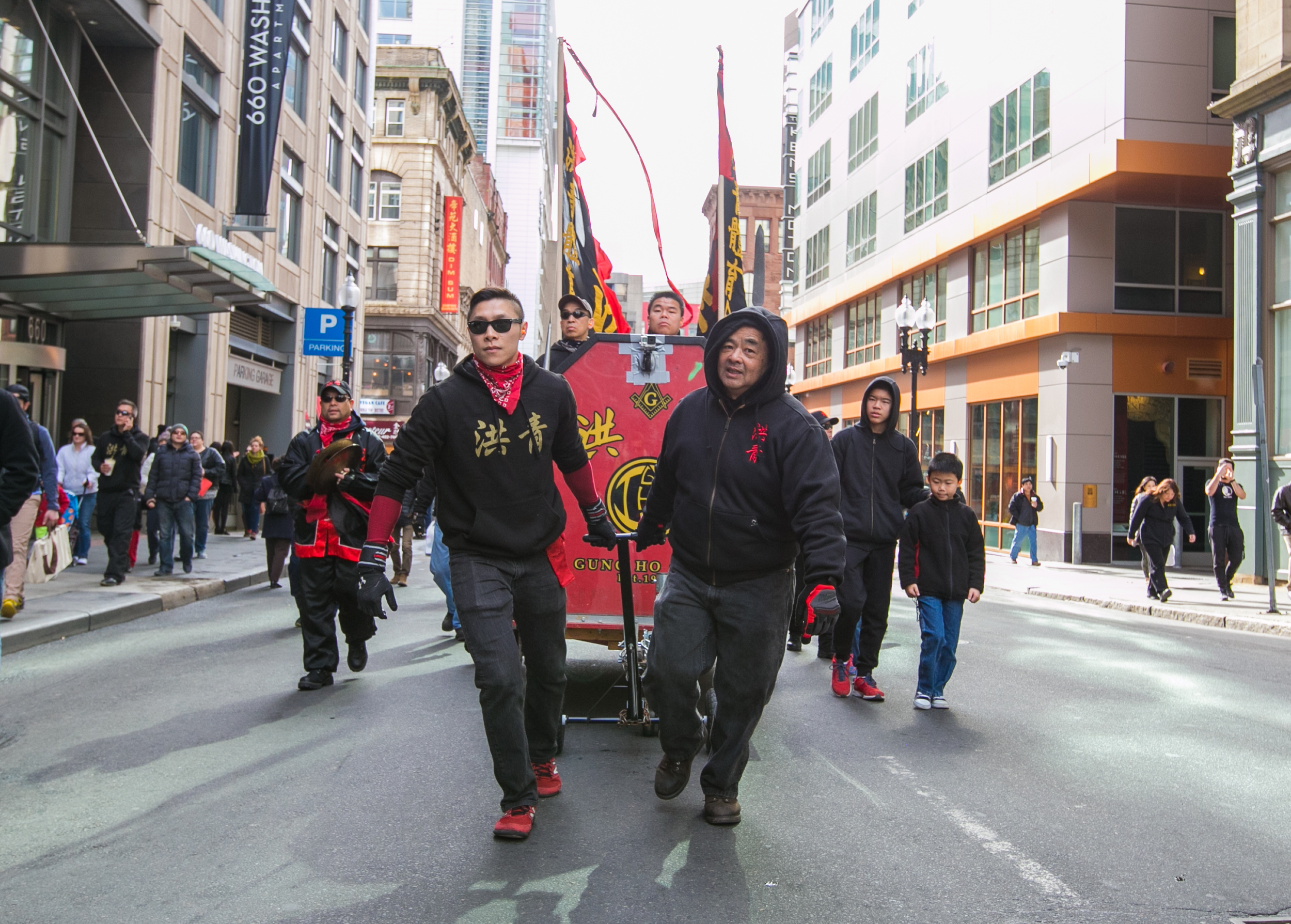 February 21, 2016: Wendell Chin (left) and Joe Chin (right) of the Gung Ho Club pull a carriage outfitted with musical accompaniment for the Lion Dance parade in Boston's Chinatown.The musicians are responsible for setting the pace of the performance,and include a drum, gong, and cymbal player. The Gung Ho Club, established in 1948 as part of the Chinese Freemasons, hosts the annual celebration in honor of the Chinese New Year.  ©  Mike Schwarz