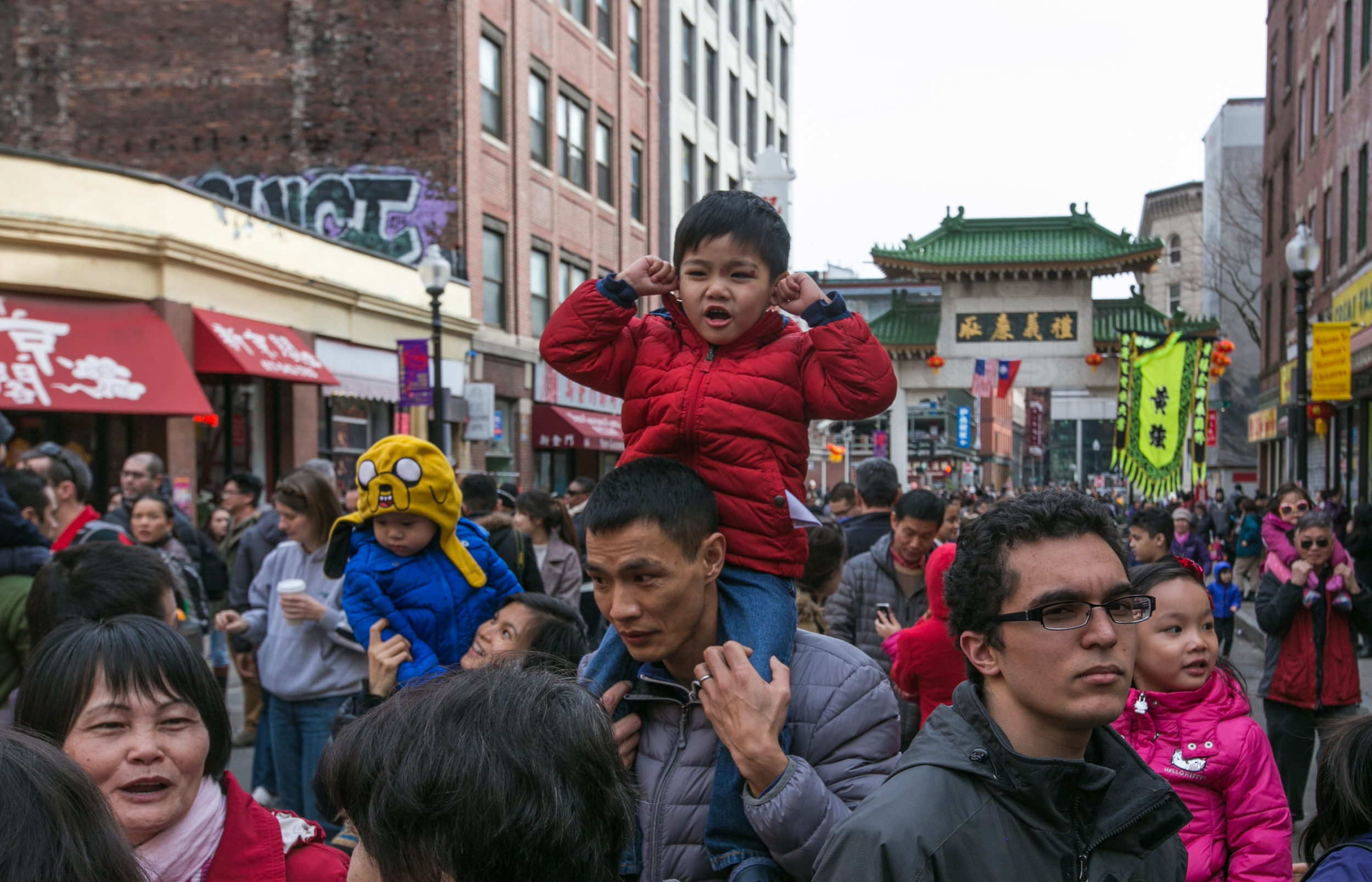 February 21, 2016: Sam Lee holds his ears as firecrackers explode during a Lion Dance performance on Beach Street in Boston's Chinatown.The celebration is organized by the Boston Chinese Freemasons in honor of the Chinese New Year.The use of firecrackers and fast-paced music throughout the festivities is believed to scare away evil spirits and bring good luck to the businesses in the year to come.  ©  Mike Schwarz