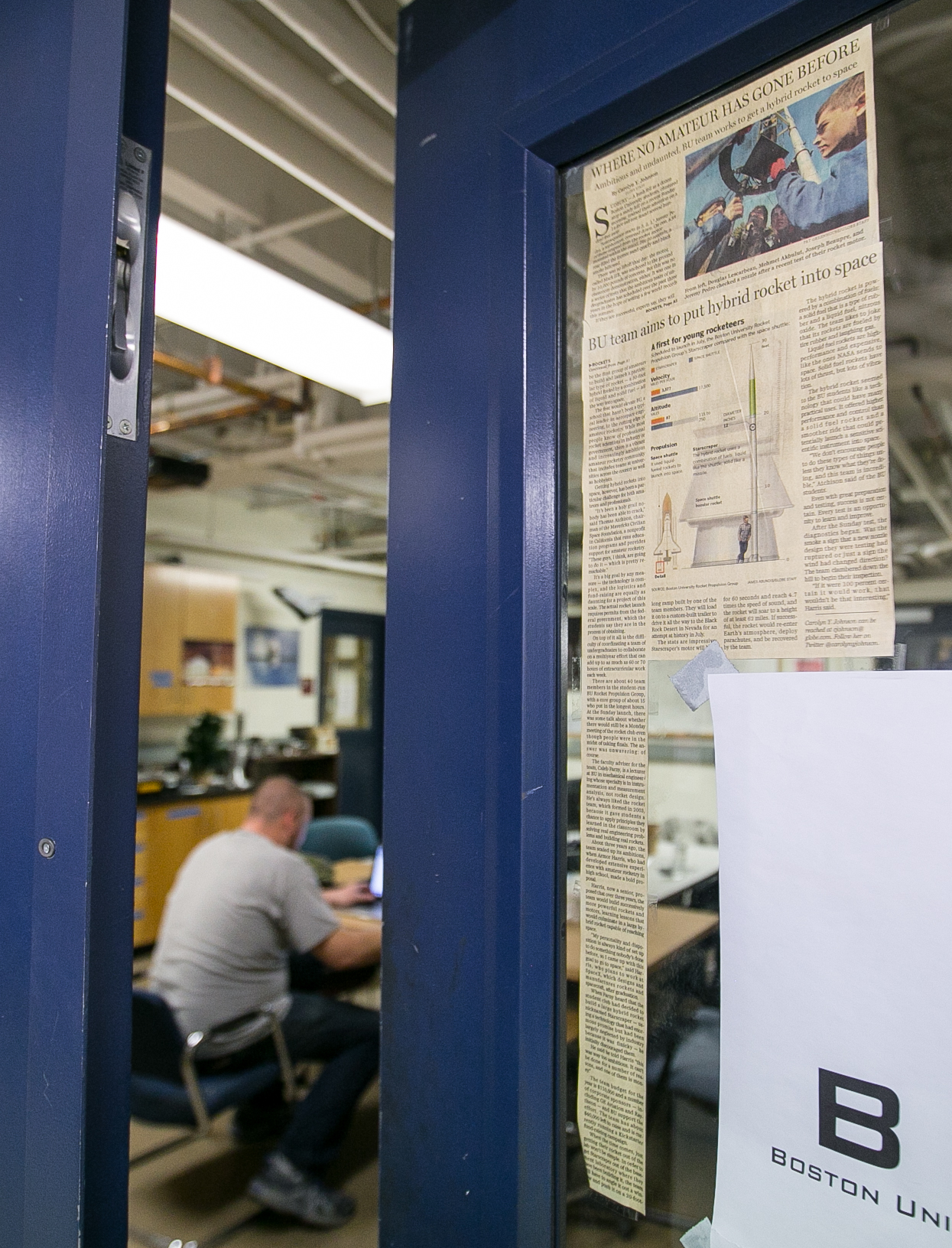 March 29, 2016 – The door of the Boston University Rocket Propulsion lab sits ajar as group member Pete Andrews works late into the night. Taped to the glass is a front page Boston Globe article featuring the team's recent accomplishments in rocket development. The group is working to assemble the newly developed liquid bi-propellant Lotus engine. Two of the Lotus engines will eventually be installed on the Starscraper, a 30 foot 1200 pound rocket, and launched from the Black Rock Desert in the summer of 2017. The Boston University team is in a tight race with the University of Southern California to be the first student designed and constructed rocket to reach space – or 62 miles above the earth's surface. ©Mike Schwarz