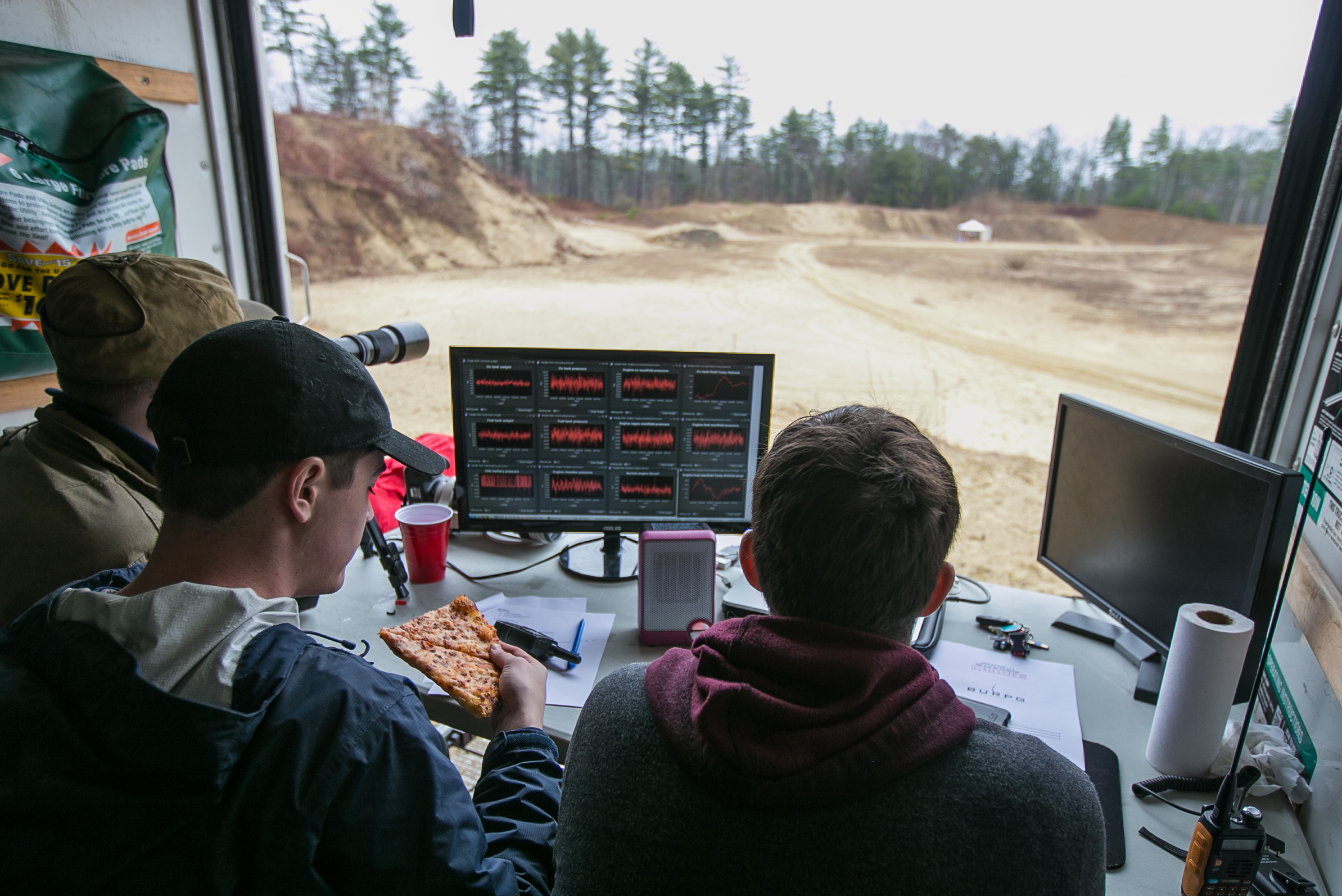 "April 2, 2016 – Jeremy Pedro (center), of the Boston University Rocket Propulsion Group, grabs his first slice of pizza as data is recorded after the first successful ""hot fire"" test of the day. After three aborted attempts, and seven hours of prep, a two-second burn of the newly developed Lotus engine was achieved. Pedro and a team of around 15 engineers had been working since 11pm the previous night to complete the test. ""We didn't quit until 6am this morning,"" Pedro said. ""40 minutes of sleep, a quick coffee, and we were out here by 8:00am."" Sleepless nights like these are common for the Boston University team as they race the University of Southern California to be the first student designed and constructed rocket to reach space – or about 62 miles above the earth's surface.   ©  Mike Schwarz"