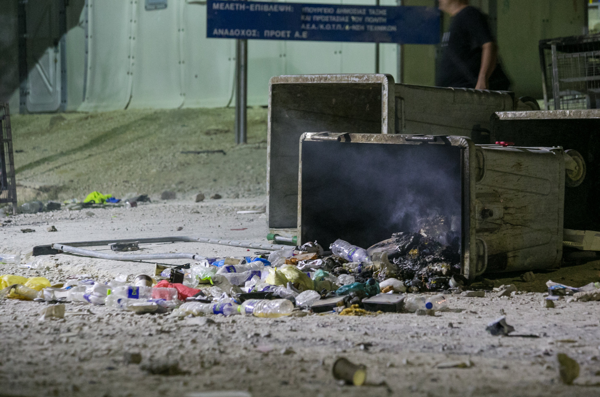 Smoldering trash spills out of a dumpster during a riot at the Moria Refugee Camp