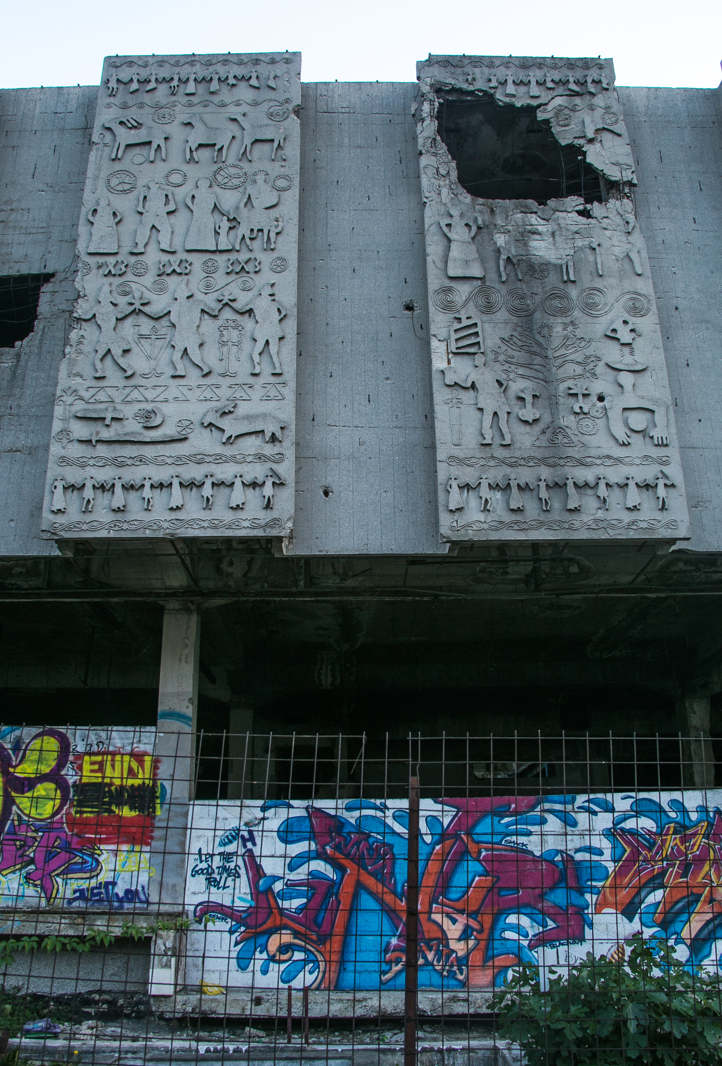 Graffiti tags on the side of a building damaged by missiles during the Bosnian War.