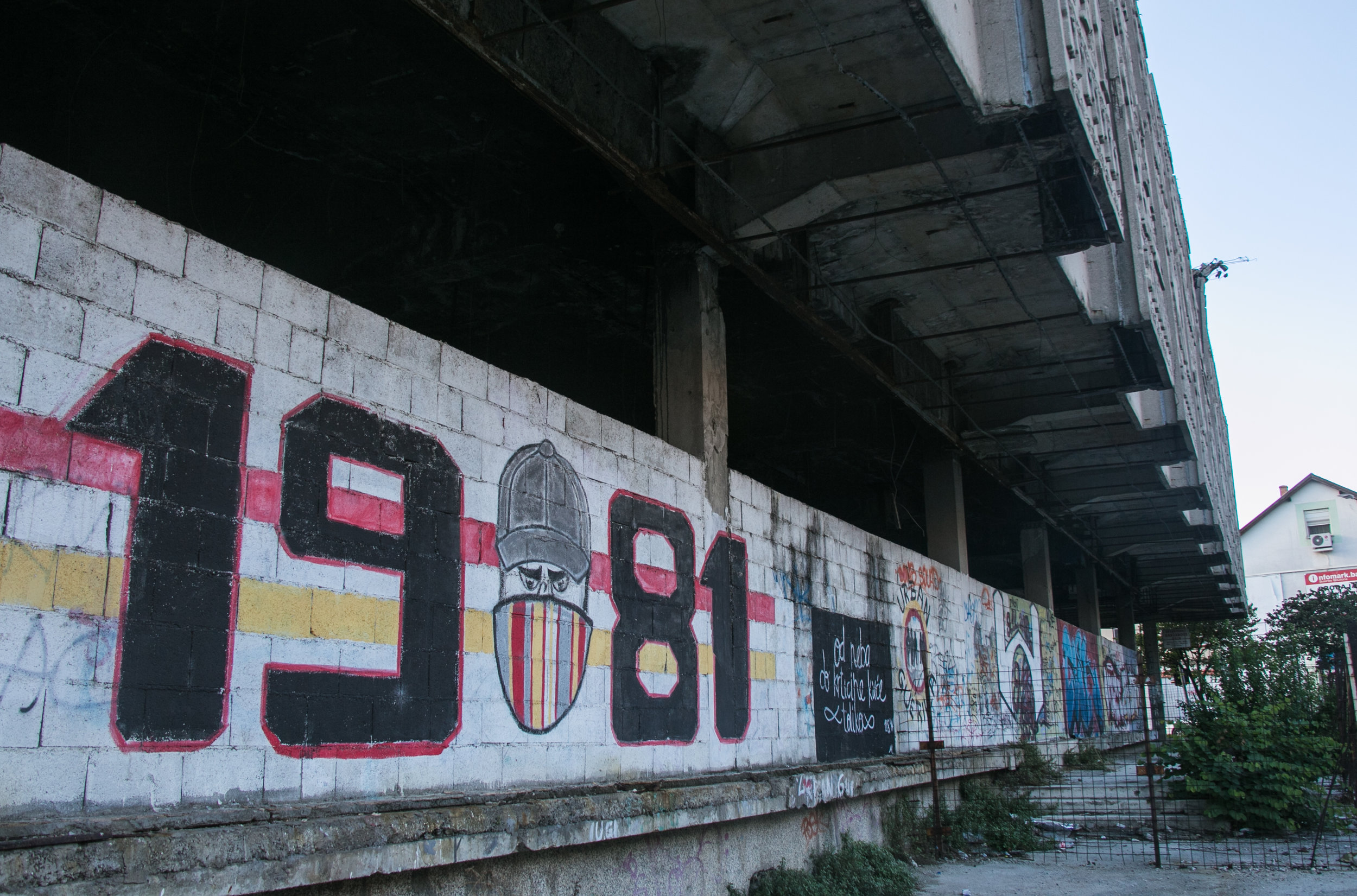 Graffiti tags on the side of building blown out by missiles in the Bosnian War.