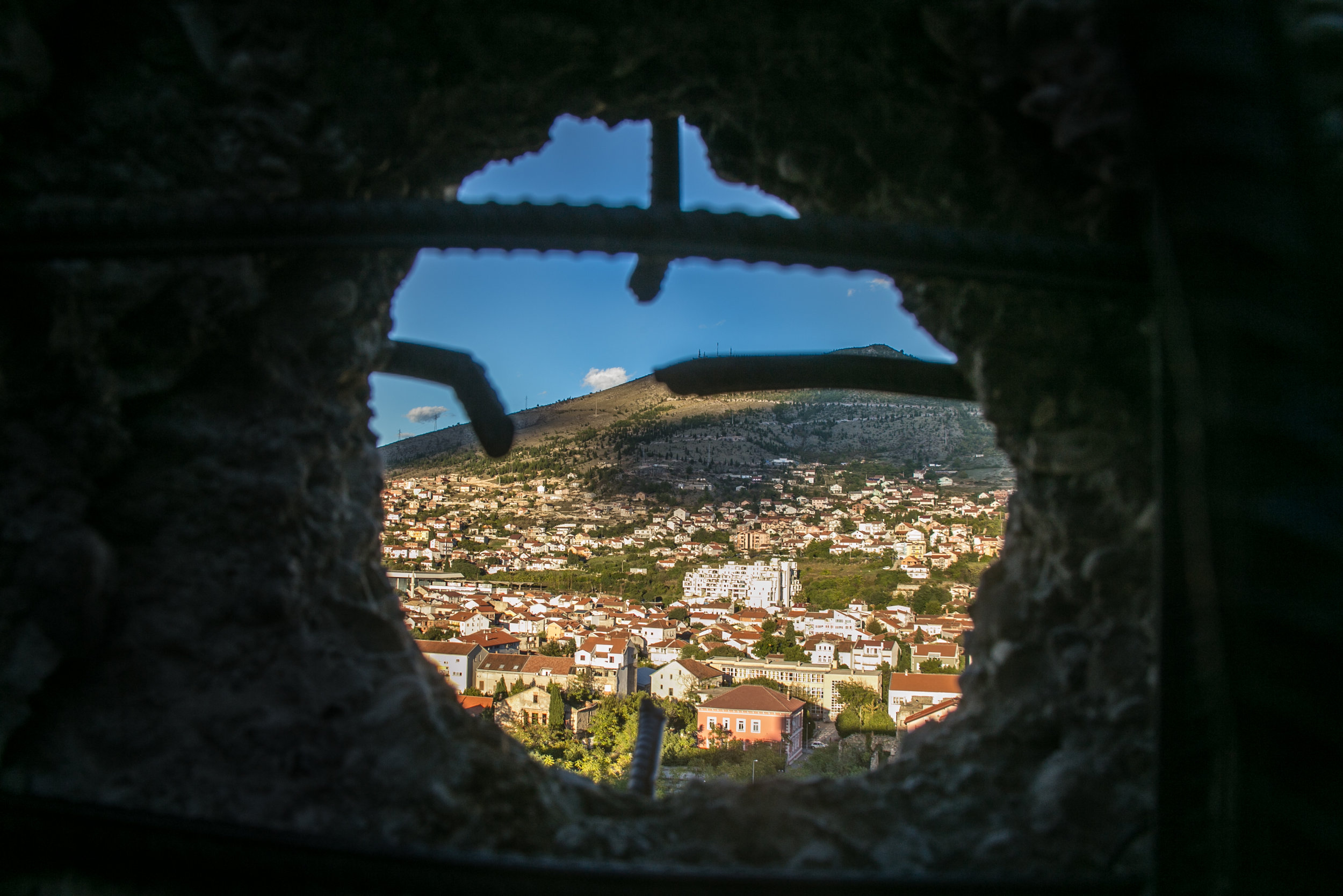 A sniper hole punched in the wall of an old bank building looks over the neighborhoods of Mostar, Bosnia. The bank was repurposed during the Bosnian War in an attempt to help defend the city from attacking Croatians.
