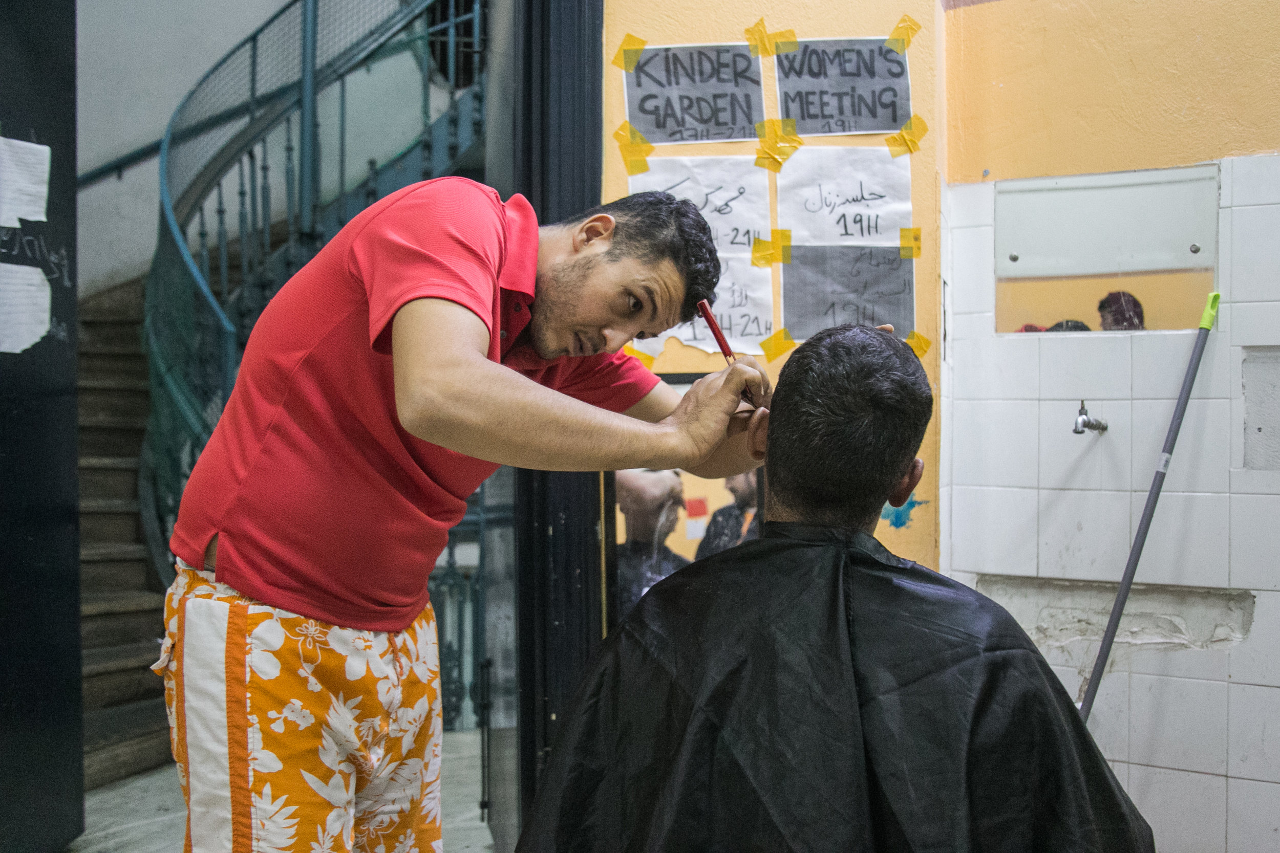 The Jasmine School barber cuts a man's hair in the hallway of the second floor. Haircuts are three euro.