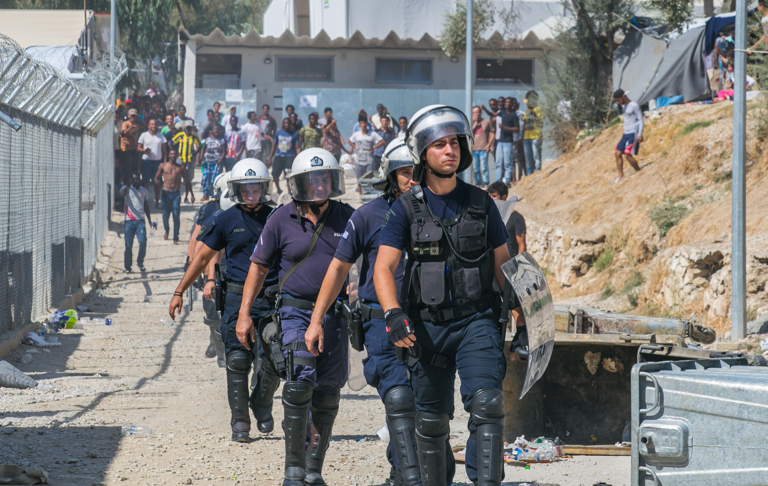 09/19/16 - 2:30pm: Greek riot police return to their compound as a crowd of migrants gathered to chant and throw rocks.