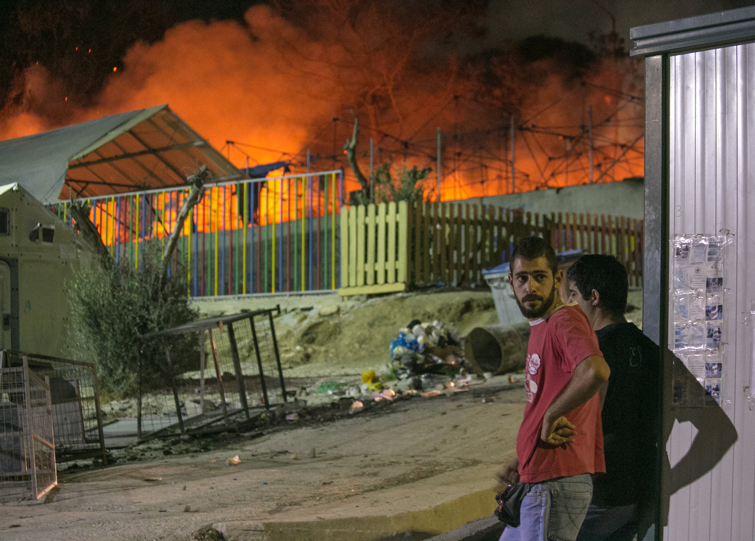09/19/16 - 9:30pm: Migrants watch on as the Moria refugee camp burns to the ground. ©Mike Schwarz/AP