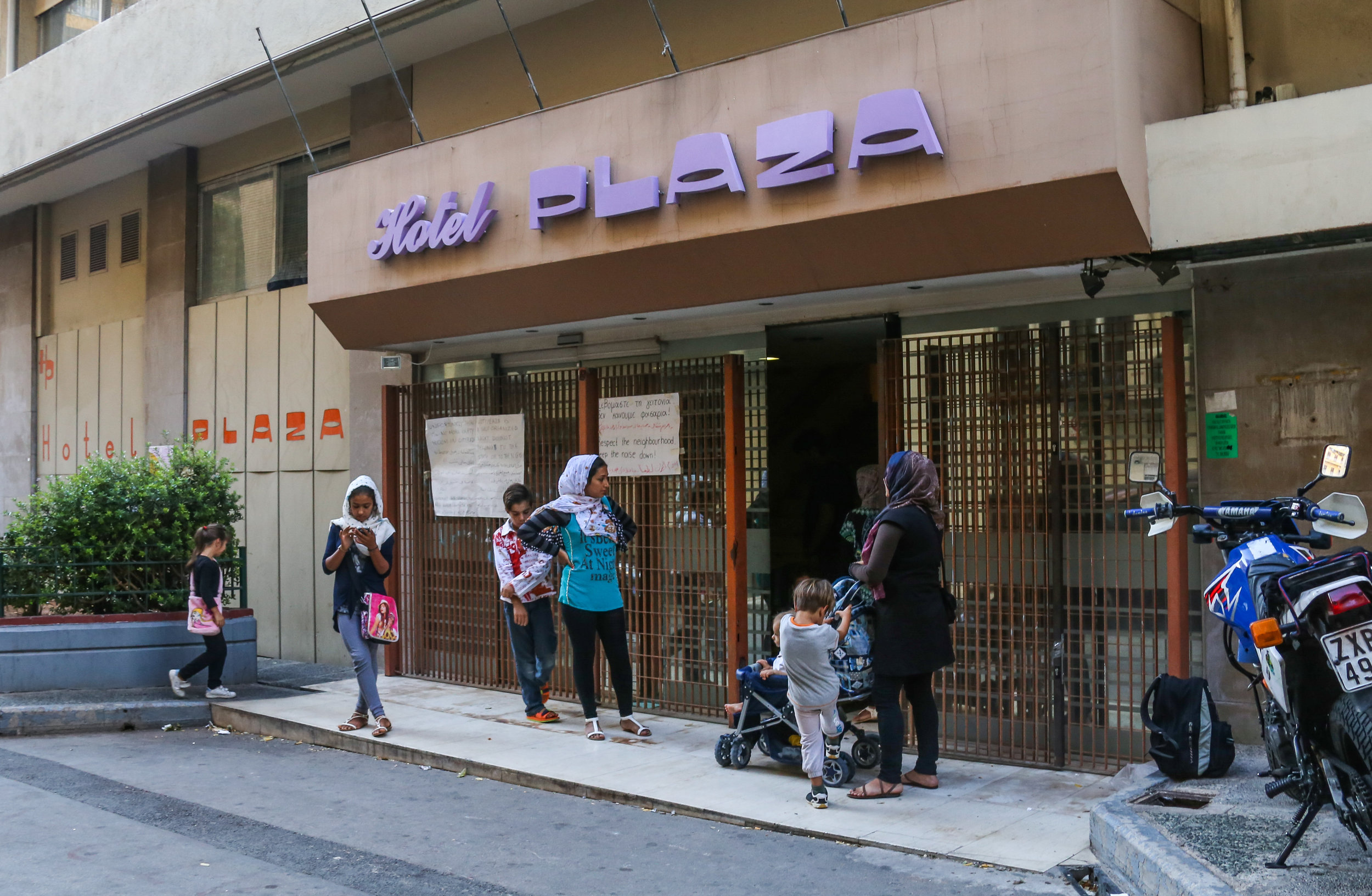 09/24/16 - 2:00pm: Mothers and their children stand outside while the lobby of City Plaza Refugee squat is cleaned. The abandoned 7-story hotel now houses 400 migrants (180 of those children).