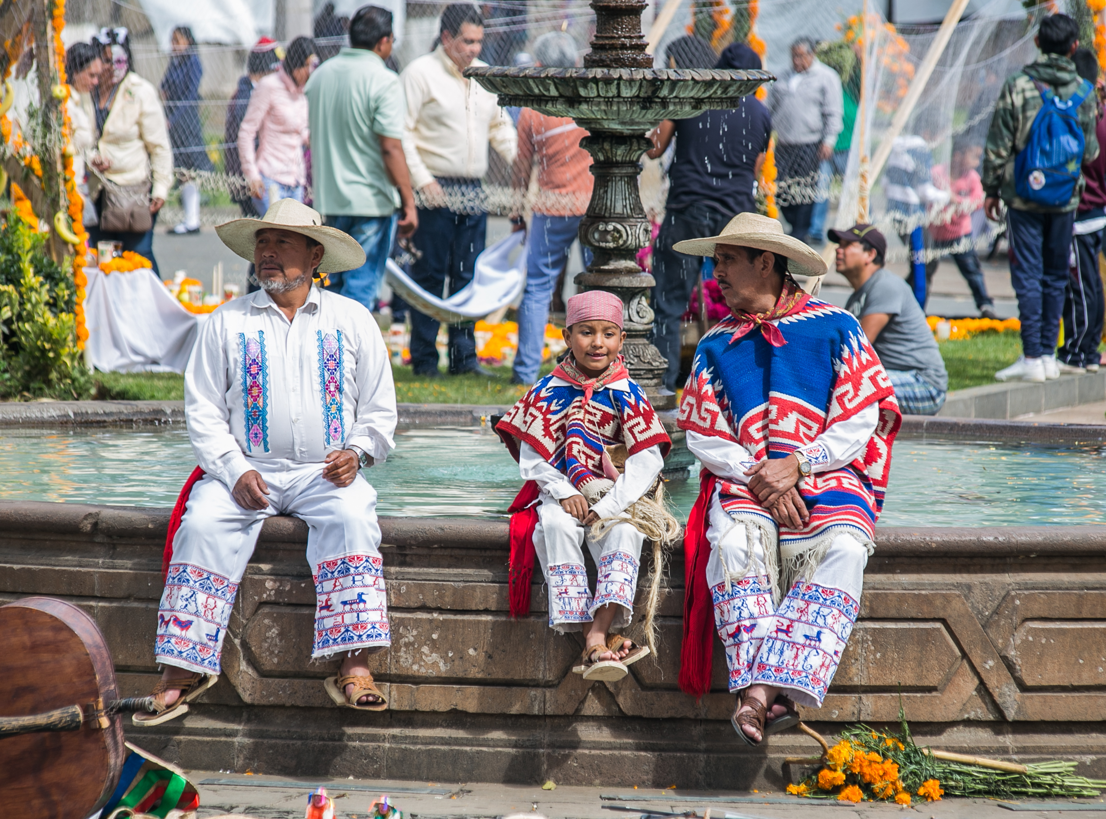 10/31/17 - 2:00pm - Dancers, dressed in traditional performance-wear, take a break on the side of the fountain in the Patzcuaro town square.