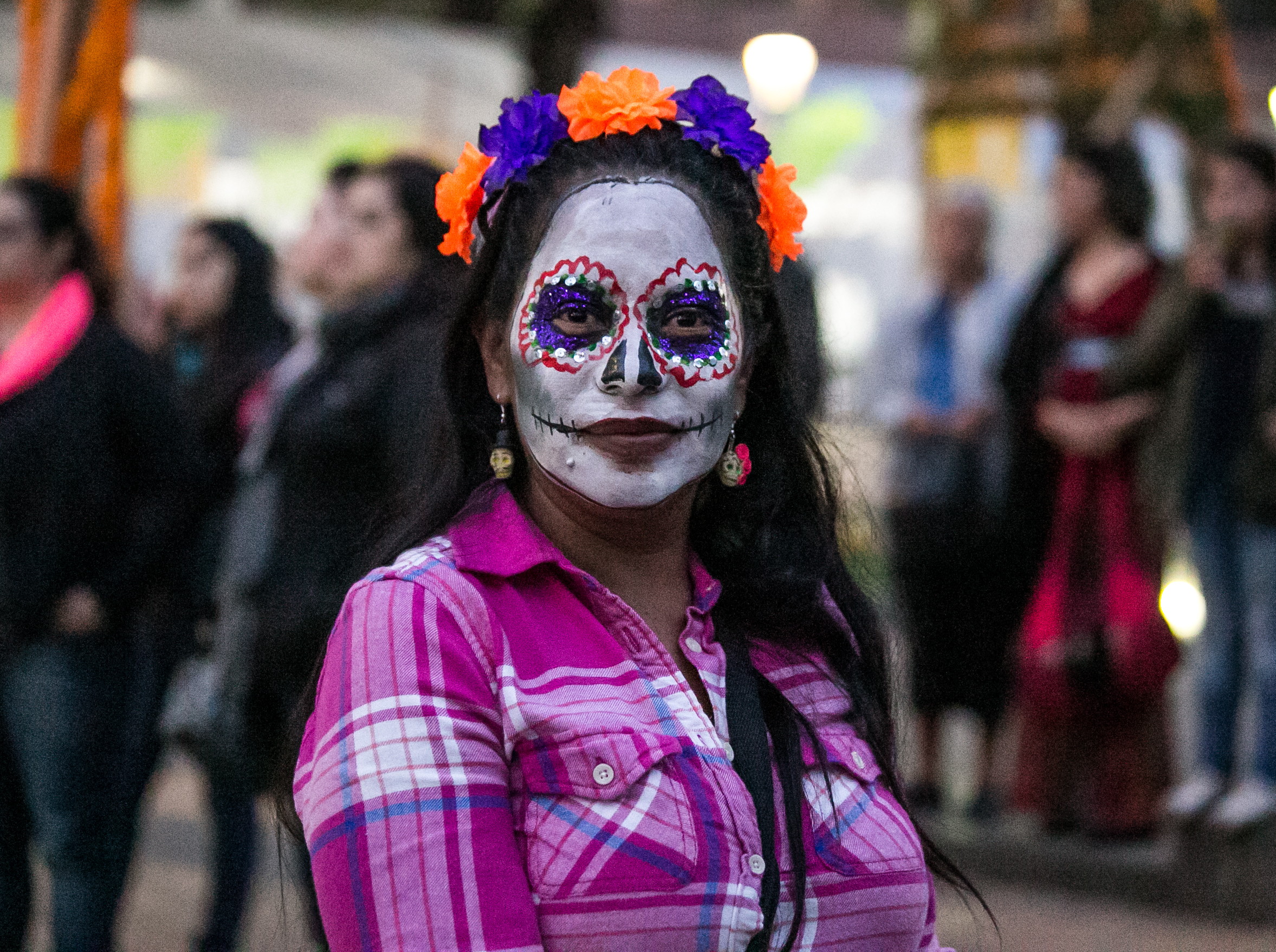 10/31/17 - 7:00pm - A woman with celebratory face paint waits to watch a traditional performance in the Patzcuaro town square.