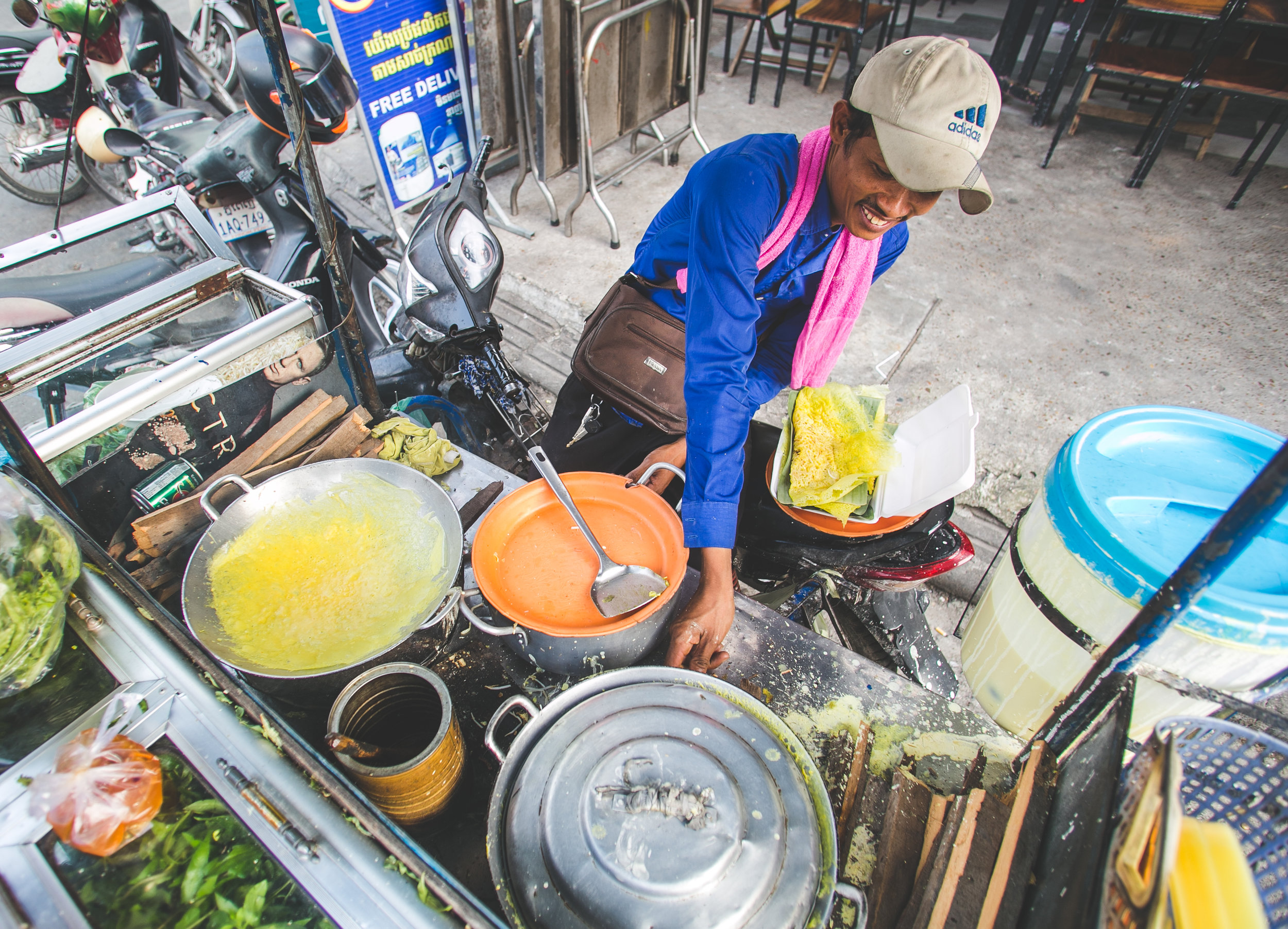 A street vendor makes Num Banh Xeo - or Khmer Meat Crepes. Authentic Khmer uses an uncooked rice mixture (instead of flour) and pork to make a crepe. It is then filled with green onions, sweet fish sauce, sugar and black pepper. The vendor was selling one crepe for about 80 cents usd.