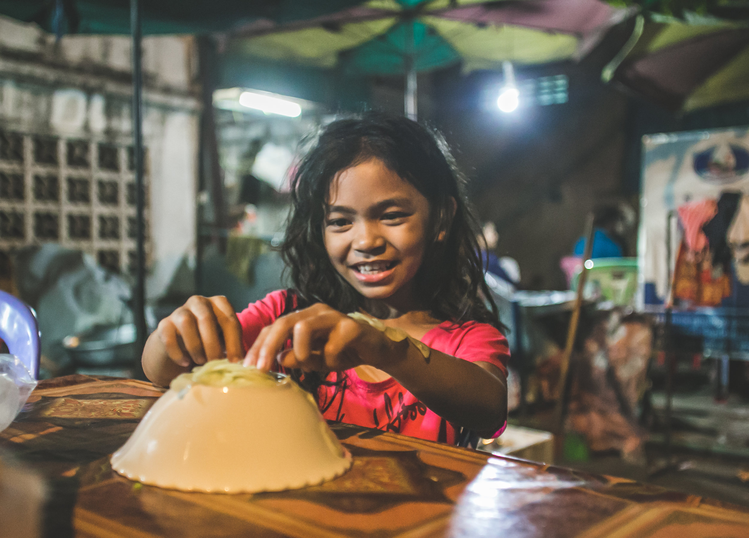 12:25am - Phnom Penh - The daughter of a local street vendor plays with onions her mother instructed her to cut up.