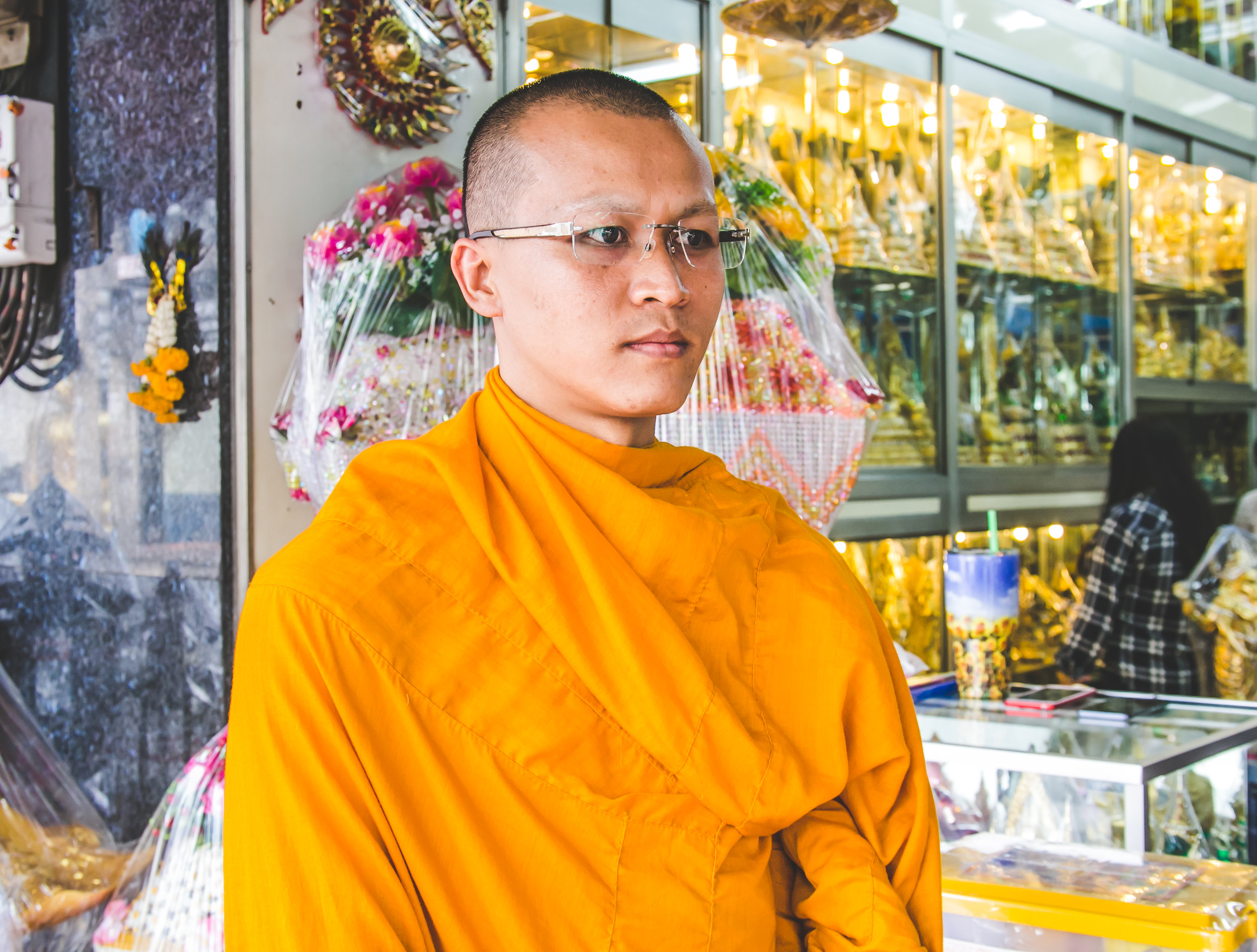 Phijit, a 32 year old Thai monk, stands outside a shop selling religious adornments, Buddha statues, and traditional robes. Phijit has been practicing for 12 years. There are over 300,000 monks, and 32,000 monasteries in Thailand. To become a monk you must be at least 20 years old, a man, and free of debt and disease. This lifestyle requires a great deal of discipline - as monks must abide by very specific set of rules (227 to be exact). These include not touching woman (even their mother), never driving a vehicle, and practicing chants, meditation, and worship techniques up to 10 hours a day.