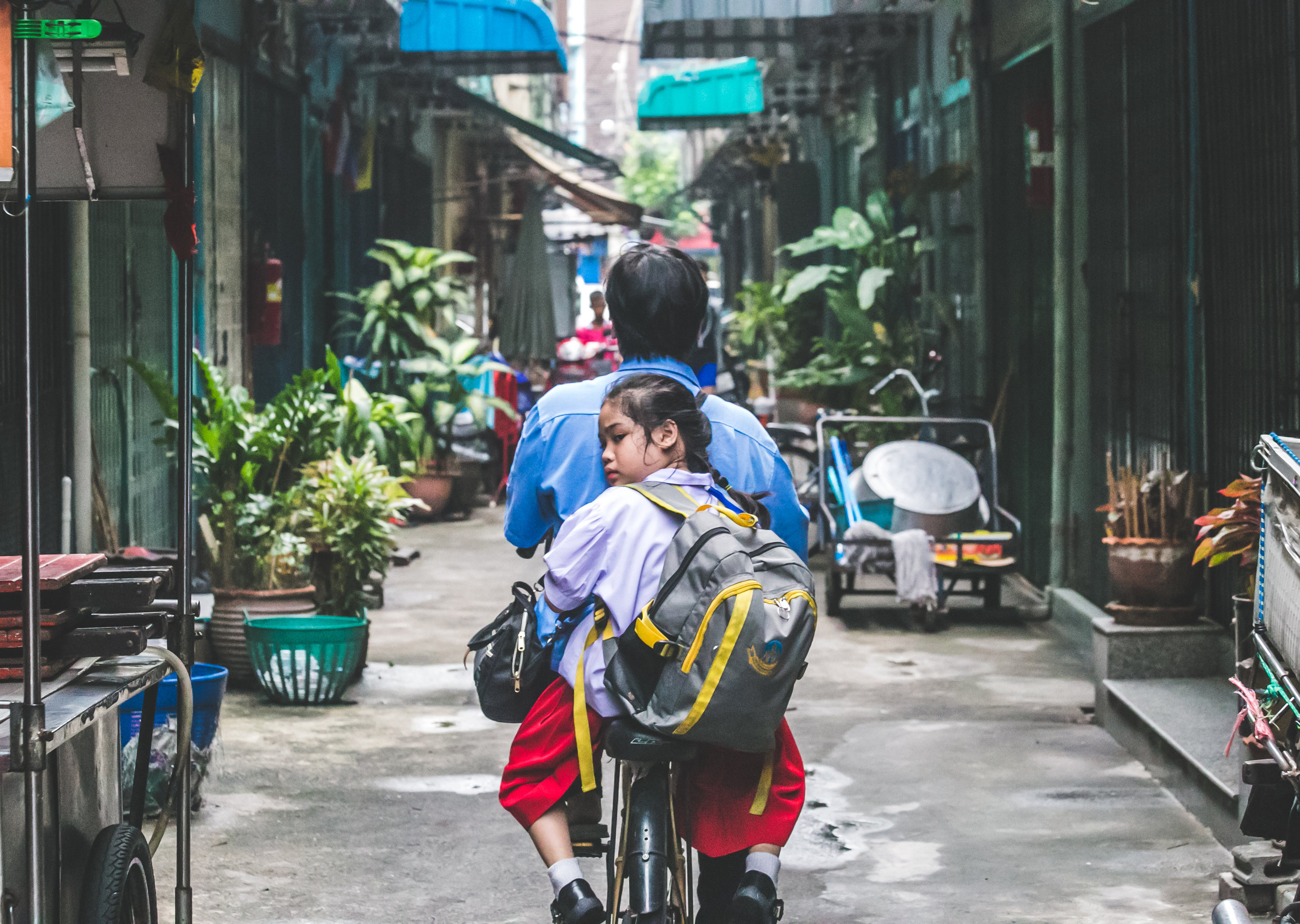 A girl holds on to the back of her father as they travel down a small alleyway on the family motorbike. It isn't uncommon to see 2-3+ people riding on the same one-person bike - especially small children.