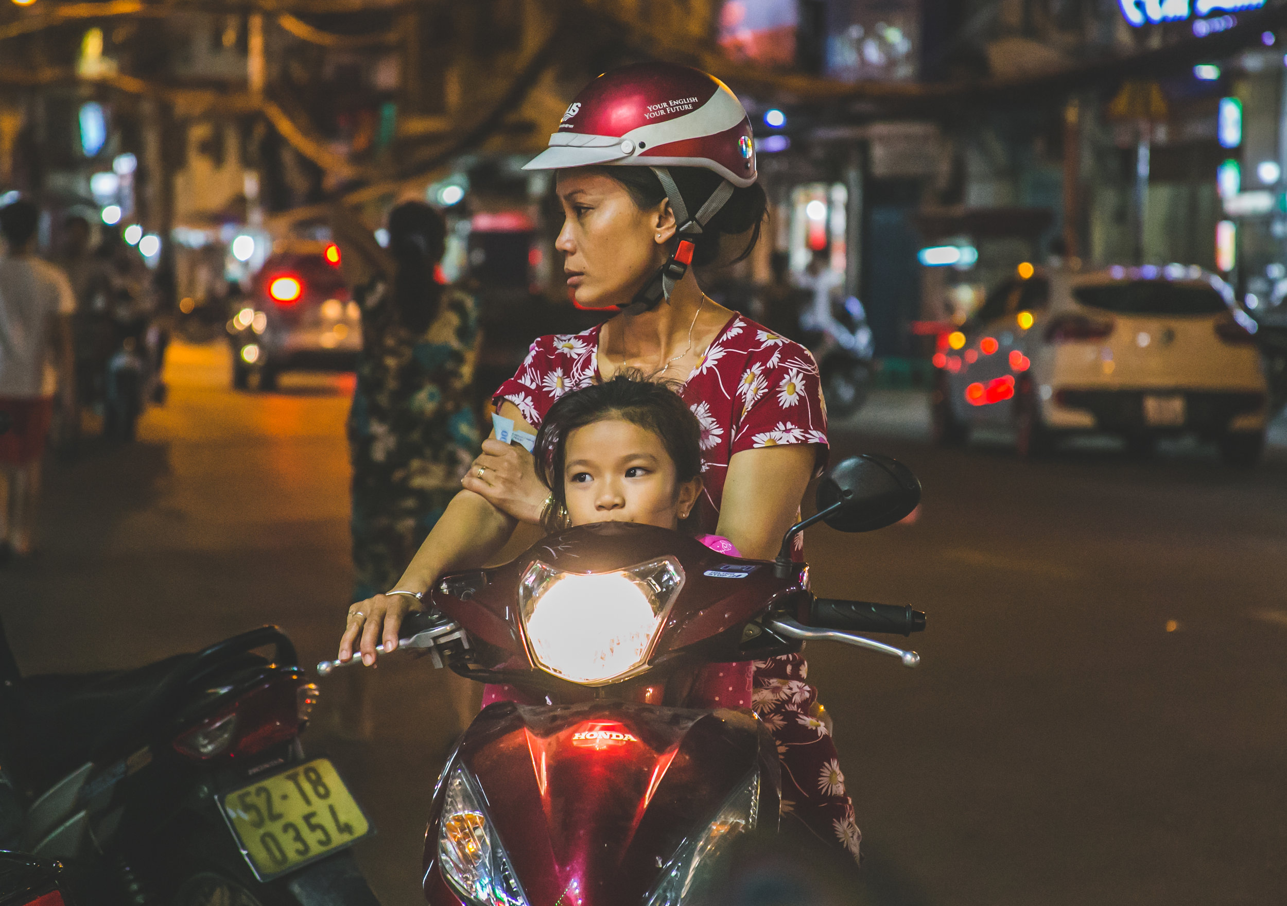 1:23am - A girl rides with her mother on a motorcycle throughout the streets of Ho Chi Minh City, Vietnam.     Ho Chi Minh now boasts over 7.43 million active motorcycles on its streets. Traffic accidents remain one of the highest causes of death in Vietnam - 30 times the number of people killed by pandemic diseases. In 2015 - 702 people were killed and 3,302 injured.