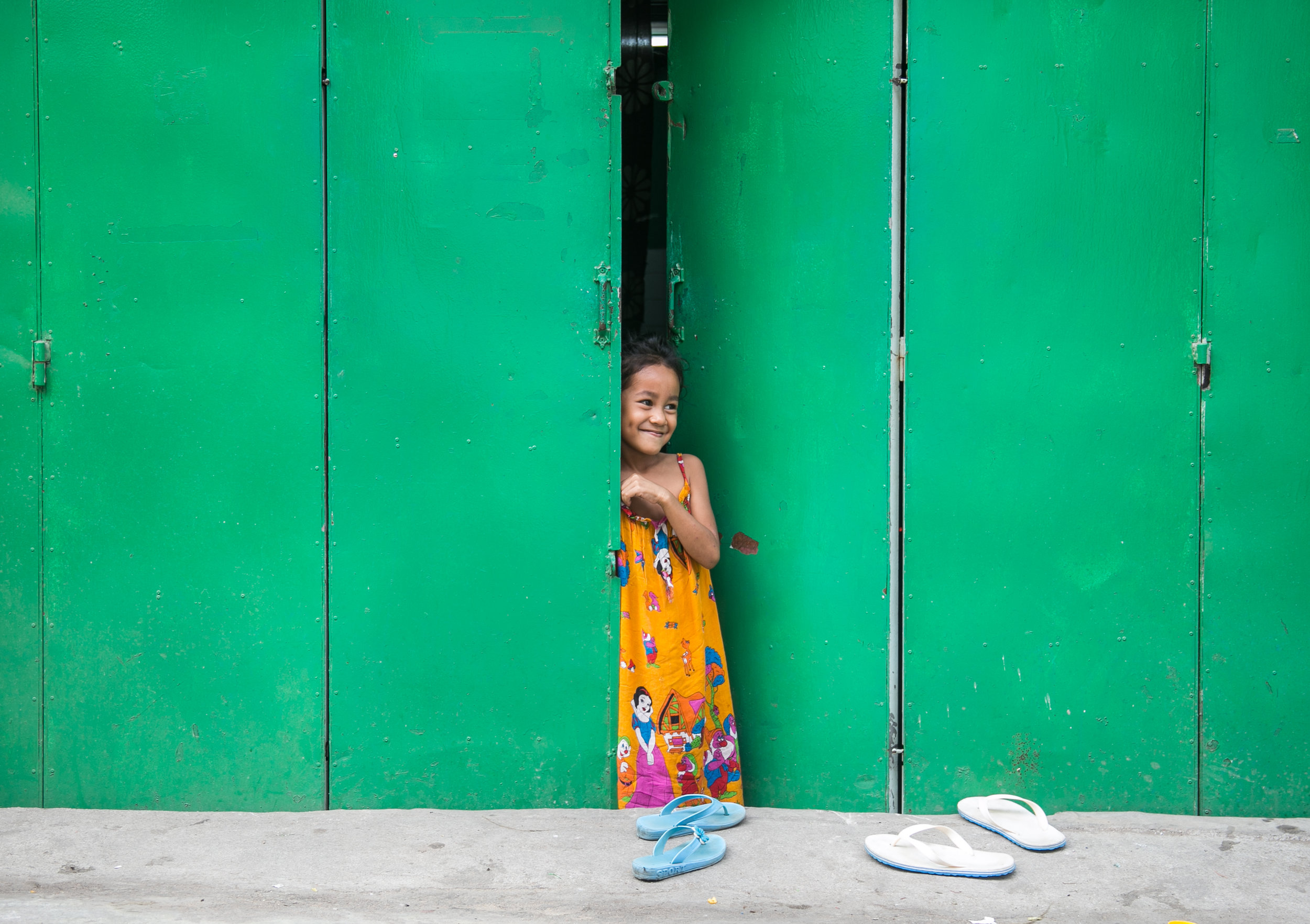 A girl smiles at her friends playing in the street in Phnom Penh's notorious street art district.