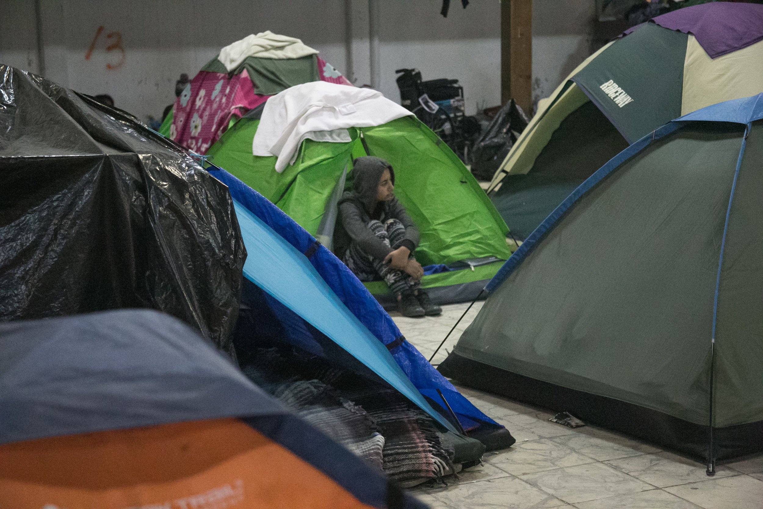 A child sits amidst the hundreds of tents packed into the Barretal compound on the outskirts of Tijuana, Mexico. The Mexican government relocated over 2,000 refugees to this facility after the first camp in Central Tijuana was closed due to intense rain, flooding, and inhumane conditions. This sheltered part of the facility houses around 500-600 woman and children - while the remaining 1,500 single men sleep in donated tents in a gated area just outside.