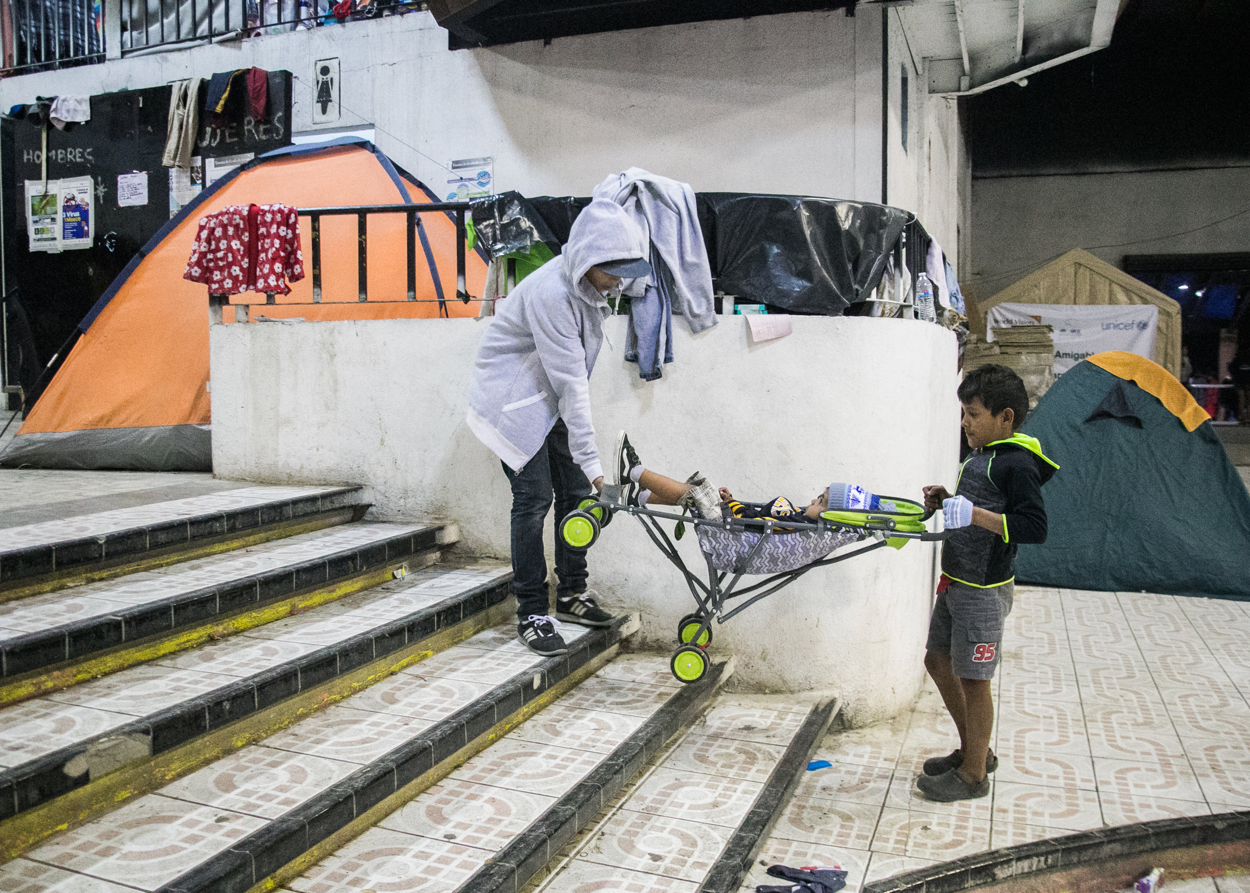 Two young boys lift their sibling's baby stroller up a set of stairs in the Barretal refugee camp. The camp is not handicapped accessible. Renovations were not possible due to the last-second nature of the migrant caravan relocation. Over 3,000 refugees were moved to other facilities after the main camp at a Tijuana baseball field was flooded out in late November.