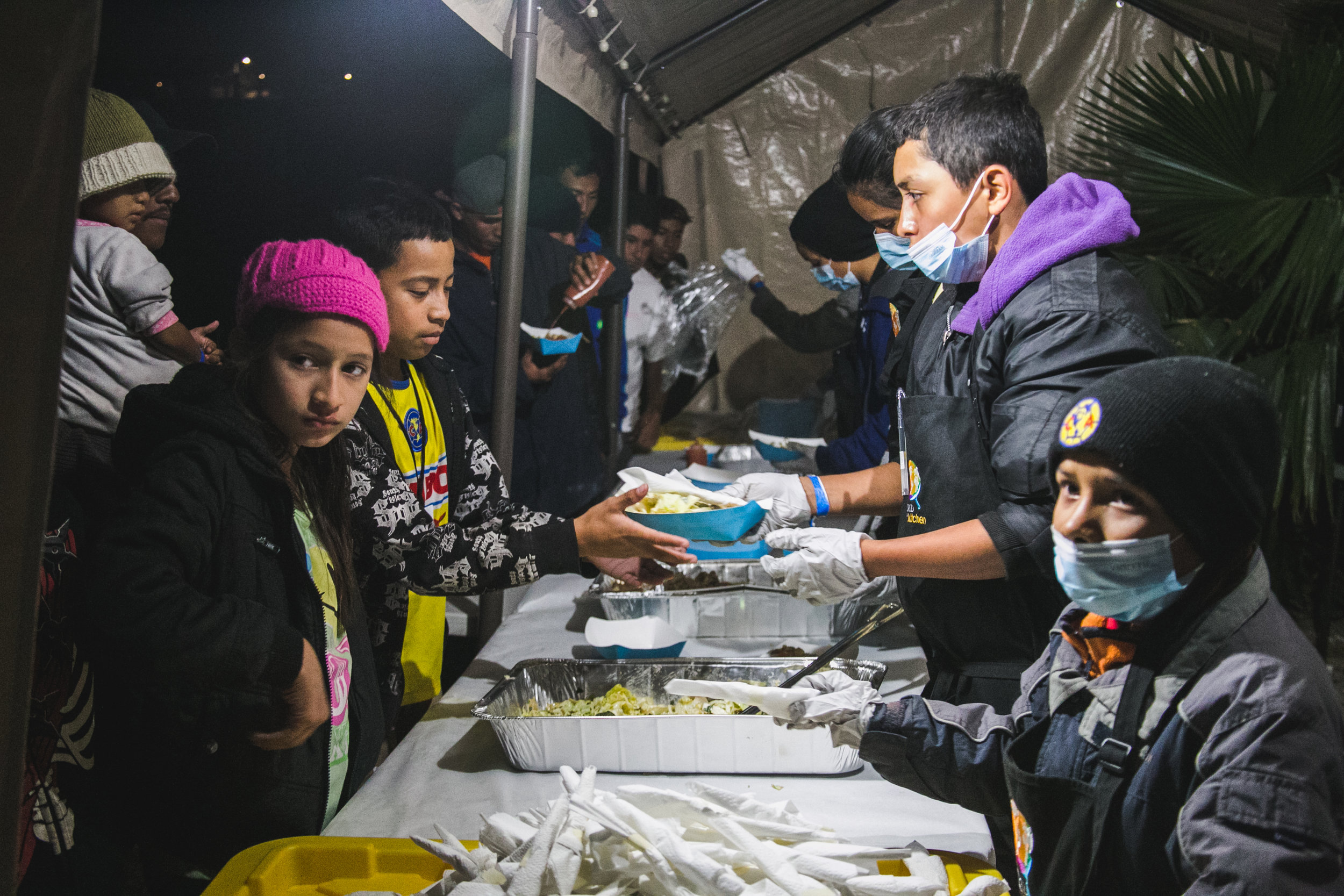 Volunteers serve dinner to over 1,500 refugees. Each day, 5-6 children from the camp would assist World Central Kitchen with serving lunch. The goal of the program surrounds creating a sustainable refugee-operated kitchen in Tijuana to serve for months (or even years) to come. The recent influx in caravan activity has drawn mass media attention - but contrary to popular belief - refugees from Central America have been arriving in Tijuana for over a decade.