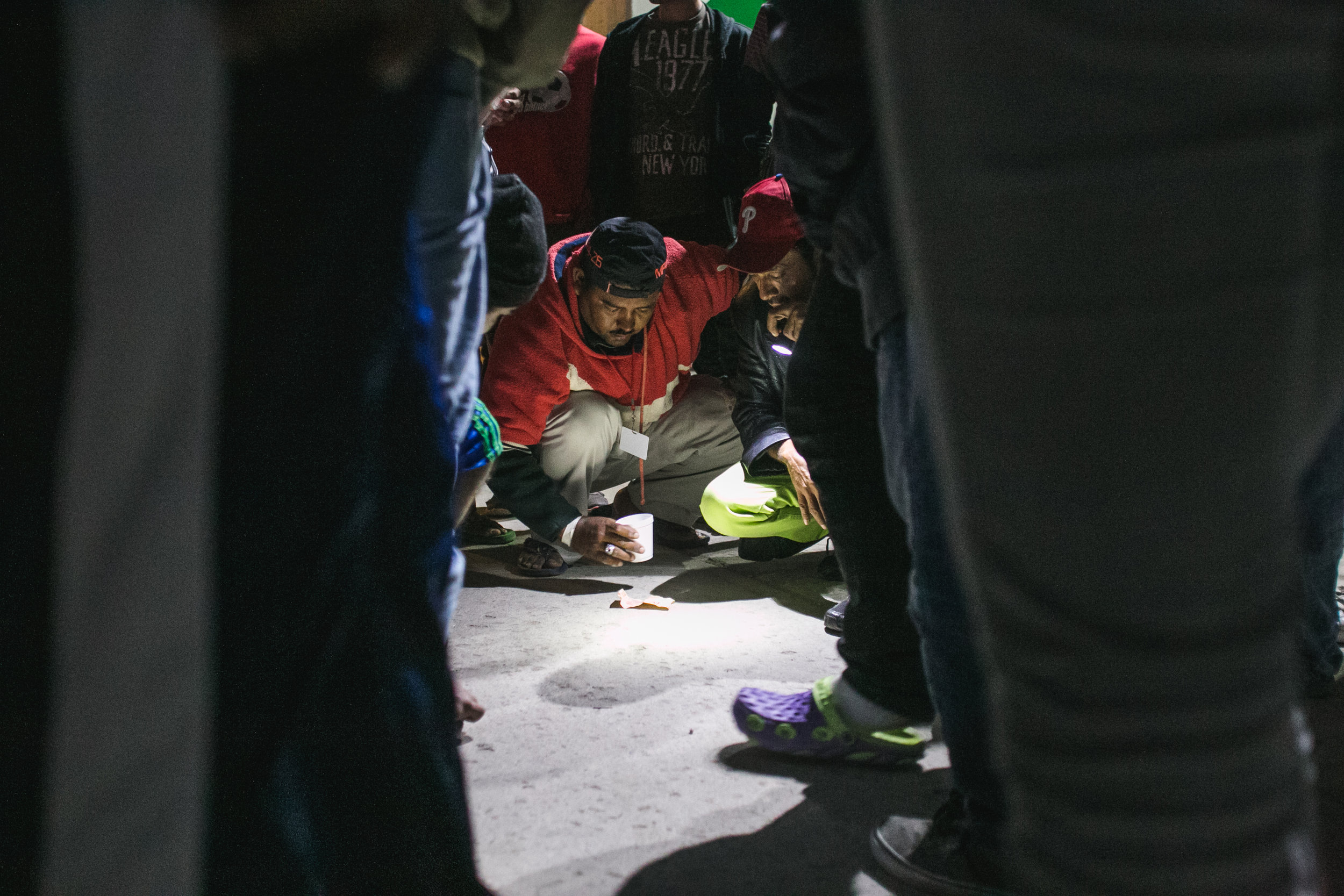 Men gamble with dice on the ground of the Barretal refugee compound located just outside Tijuana, Mexico. Gambling, soccer, and card games are among the most popular activities to pass the time.